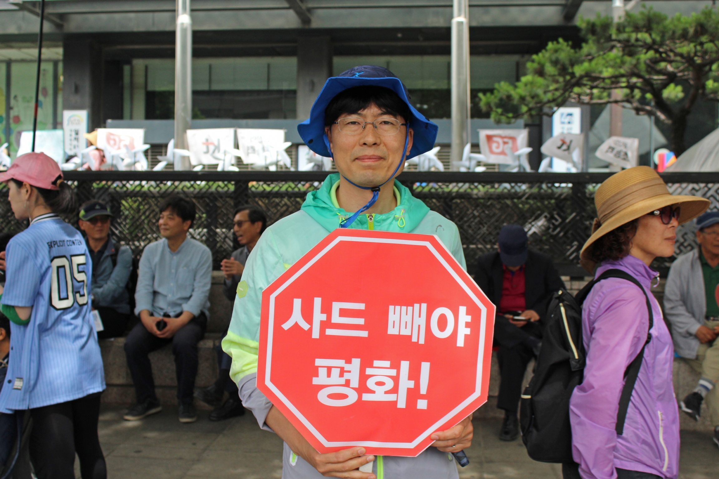 A man holds red protest sign encouraging engagement between US and NK.