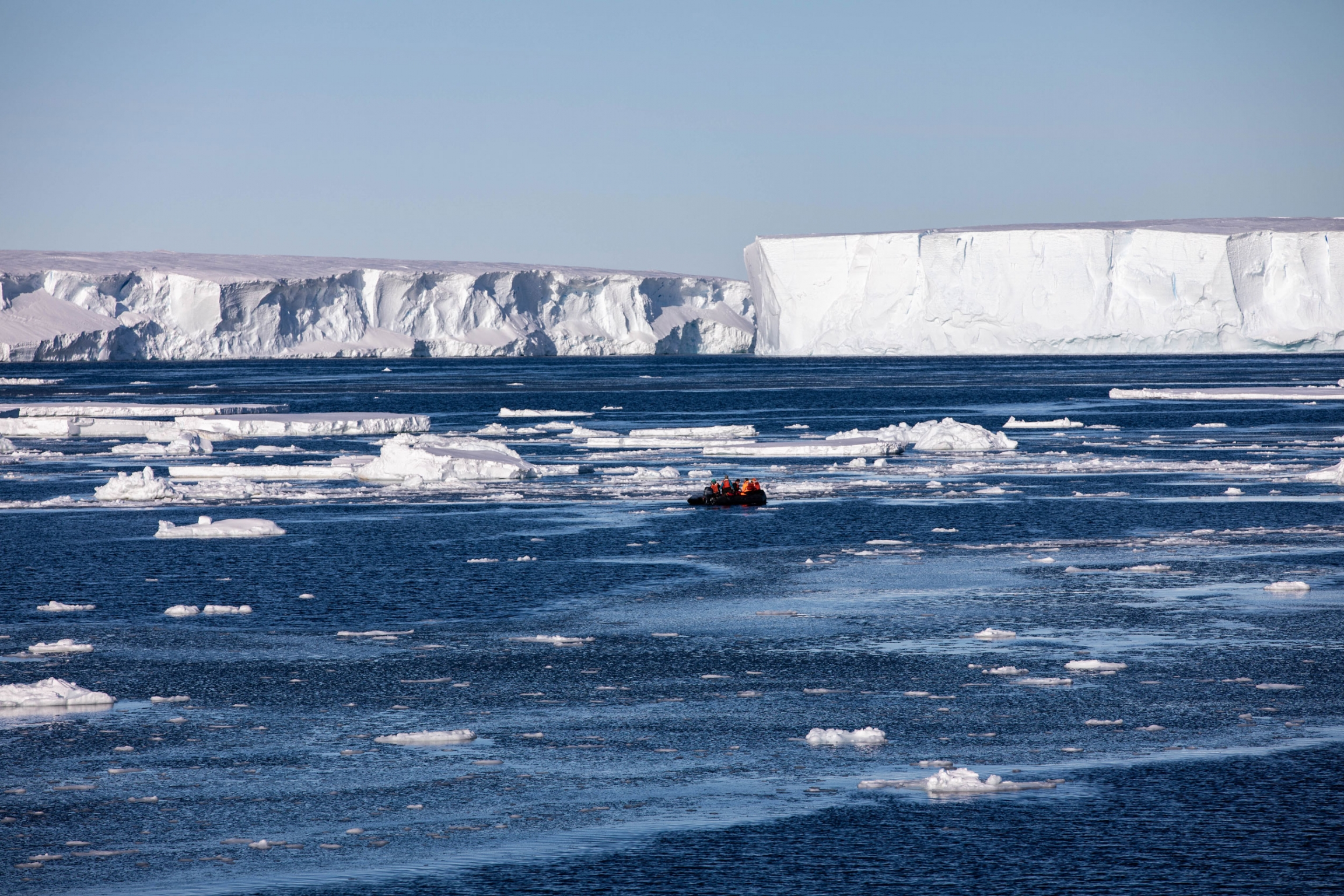 A Zodiac boat is shown off in the distance with several people aboard with large white floating ice all around.