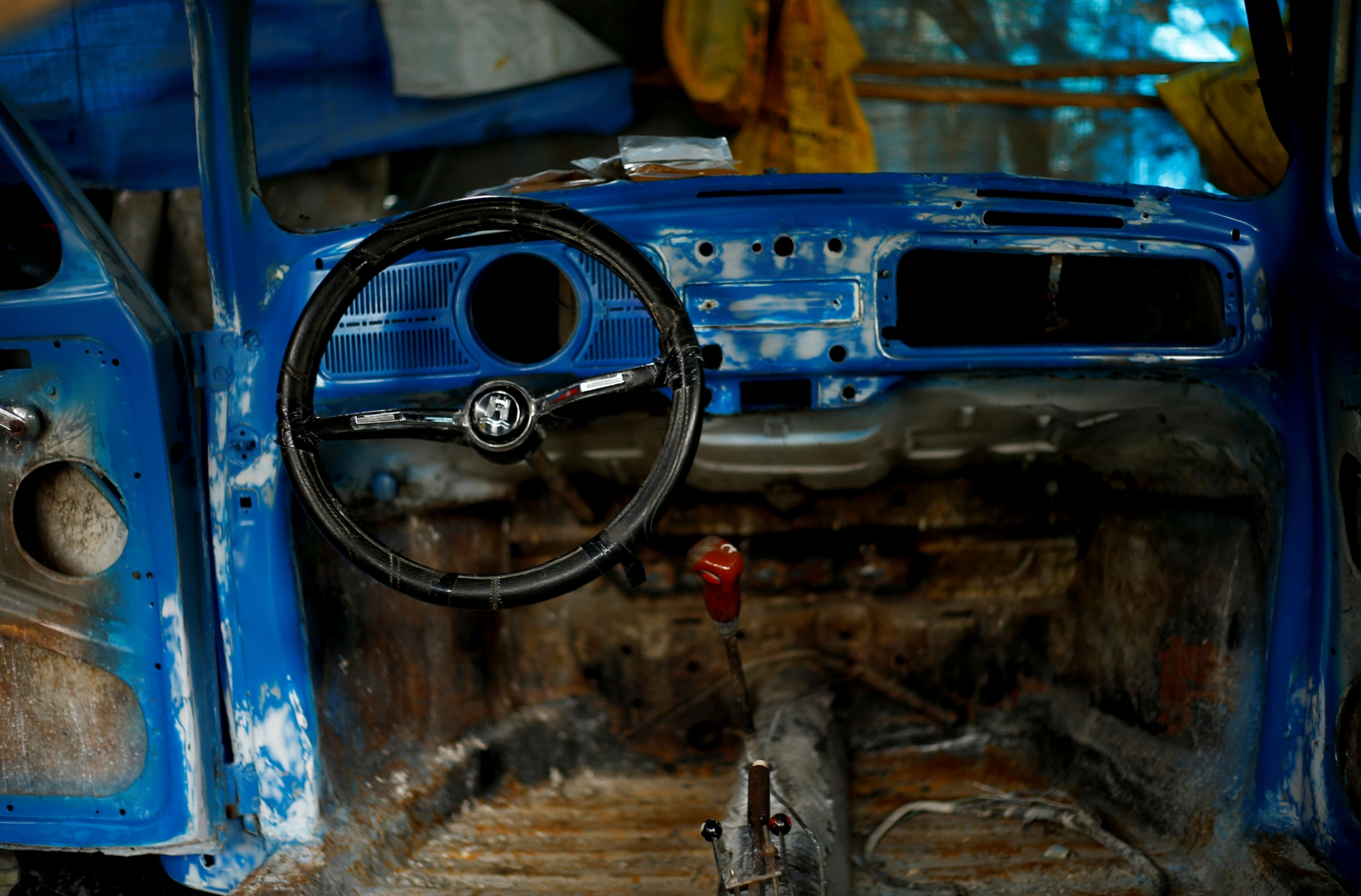 The blue, stripped down interior of a Volkswagen Beetle car is shown along with a black steering wheel.