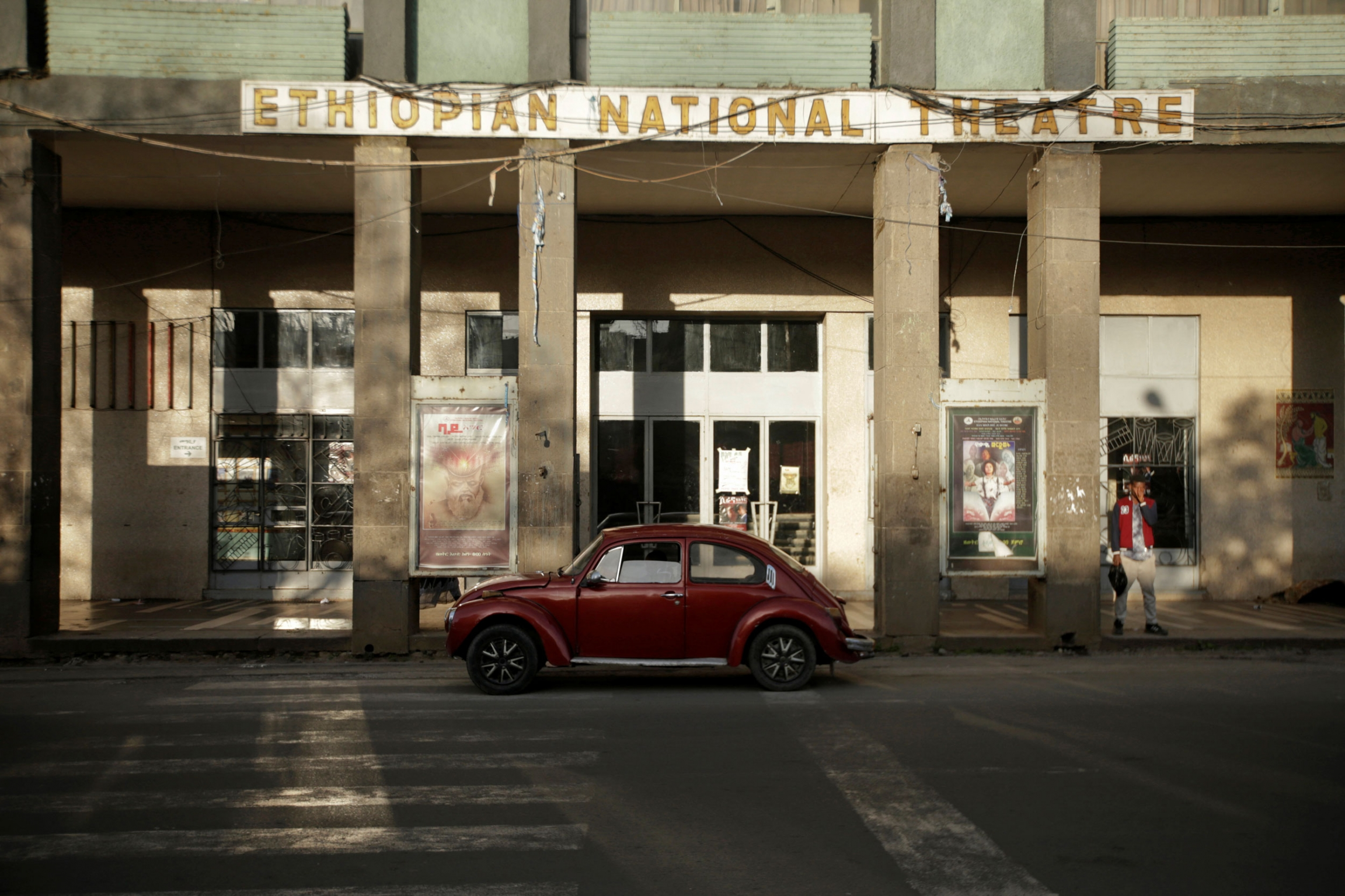 A red Volkswagen Beetle is show parked in front of the tall columns of the Ethiopian National Theatre.