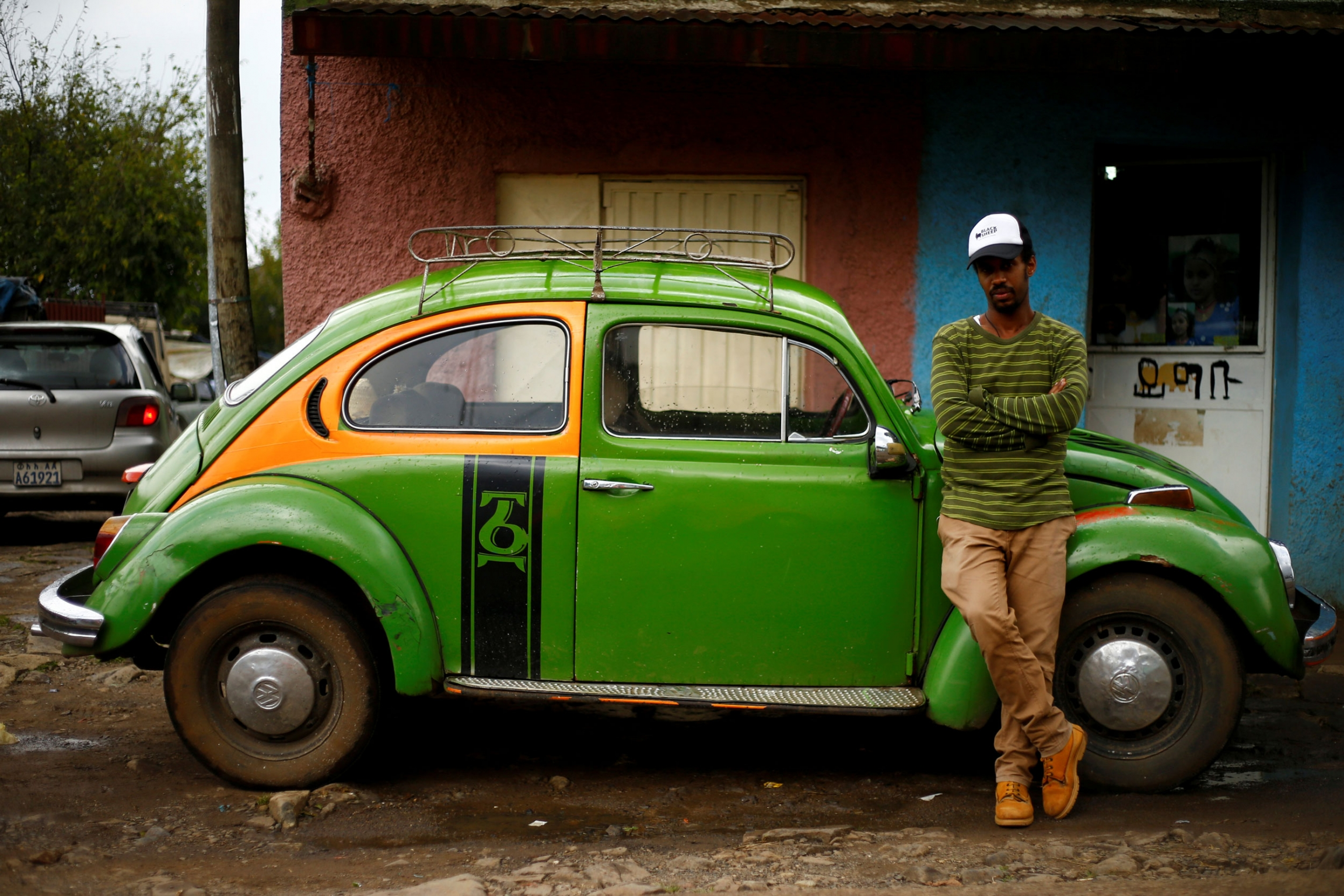 A man in a stripped shirt and hat is shown standing next to a green 1976 model Volkswagen Beetle.