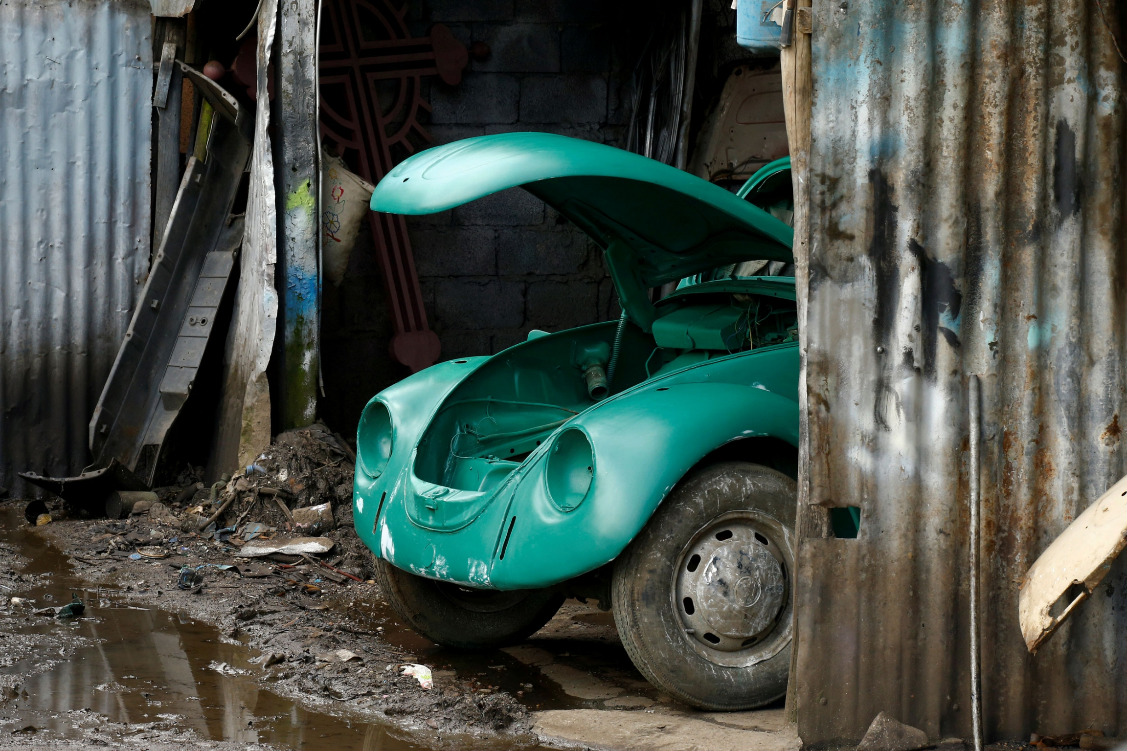 The front end of a Volkswagen Beetle is shown sticking out from a metal garage.