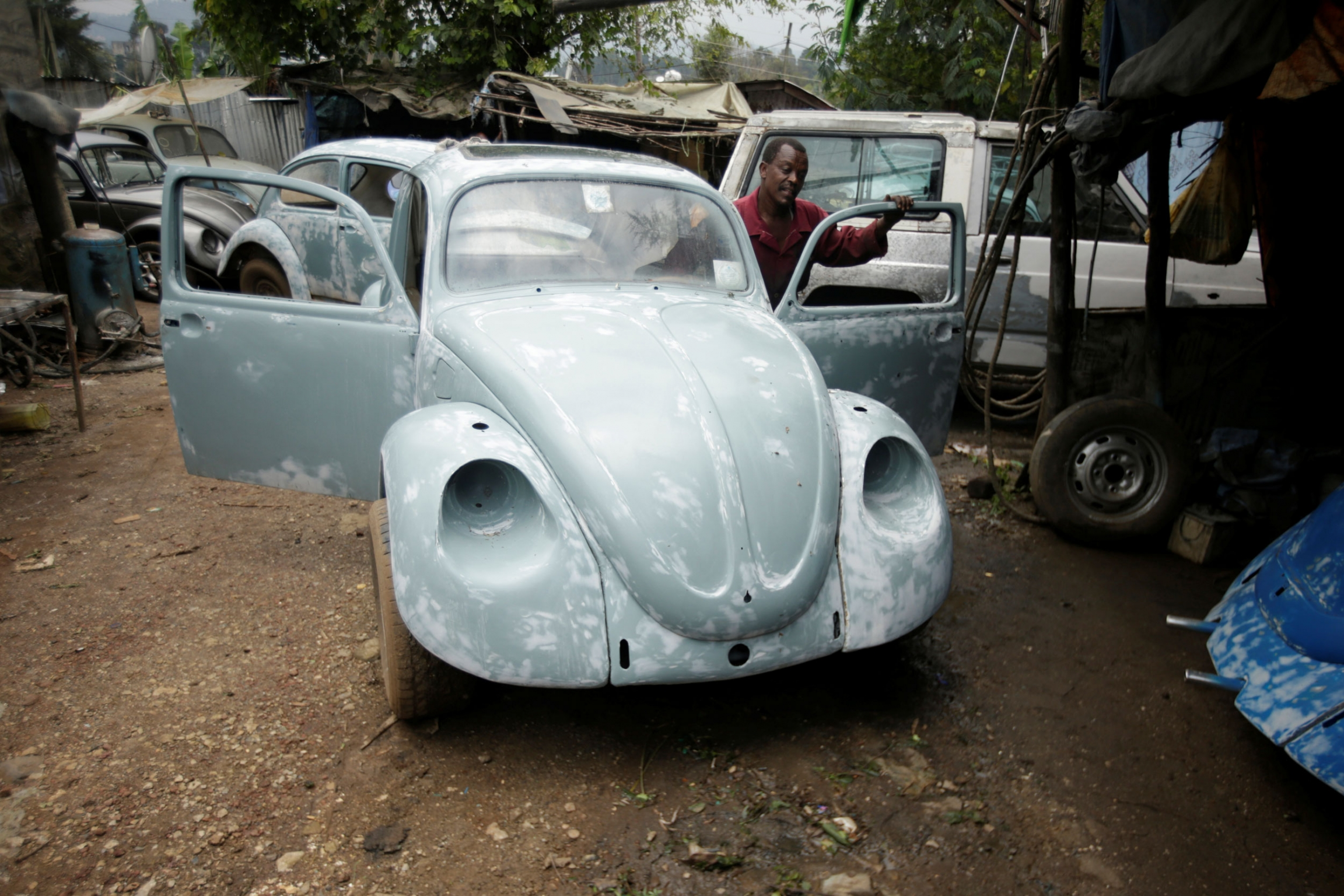 A man is shown behind an open door of a Volkswagen Beetle while he is pushing it.
