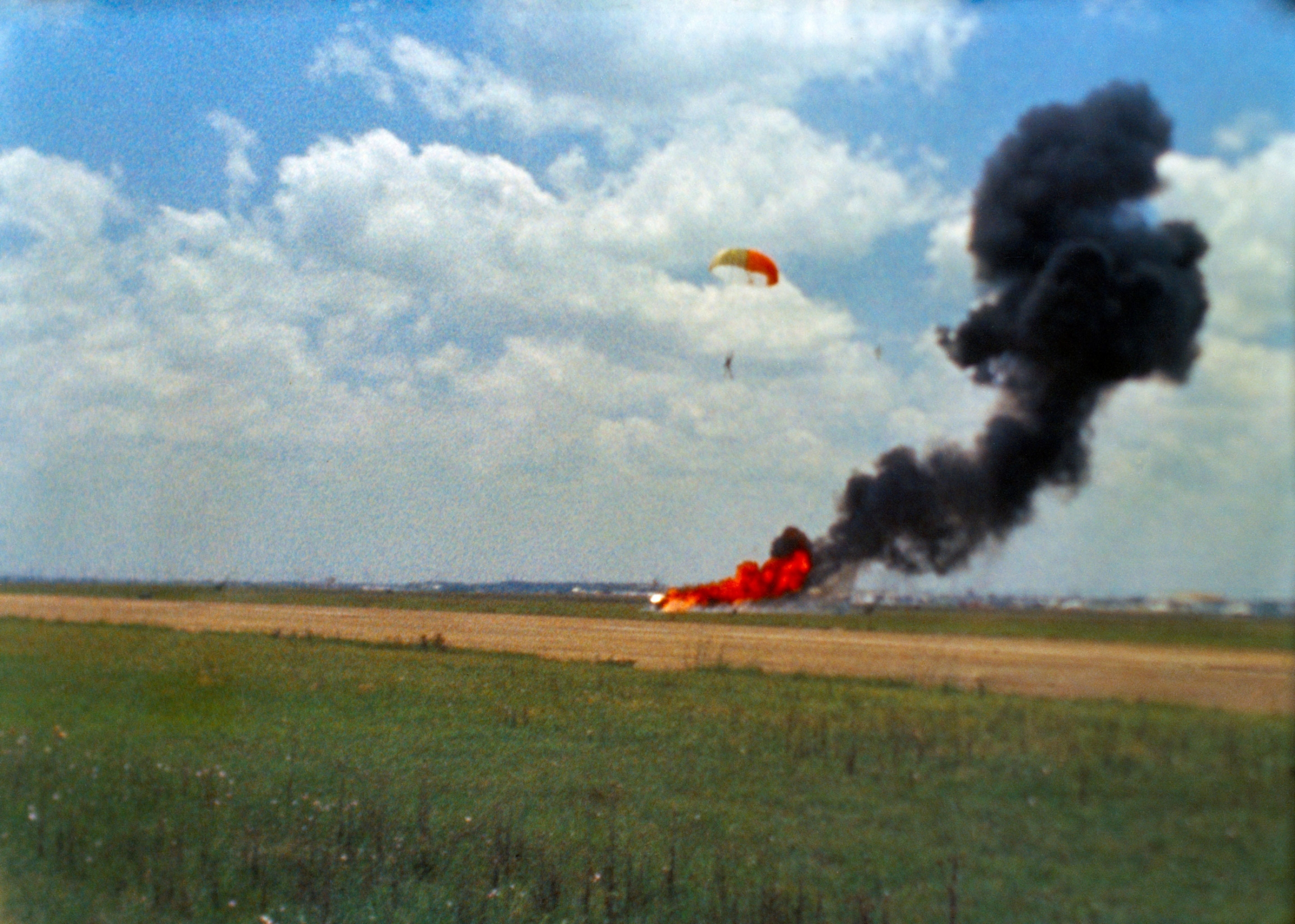 An airfield is shown with Neil Armstrong and his parachute landing.