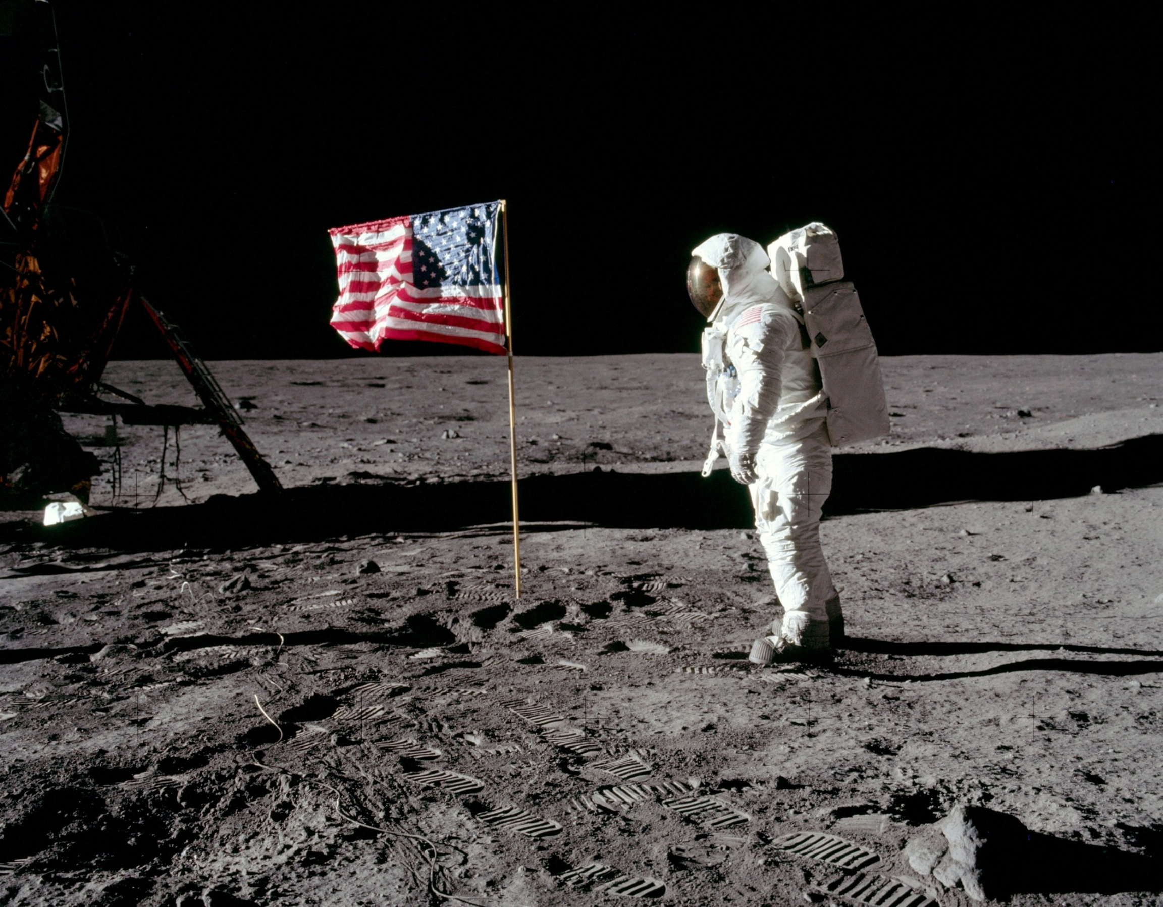 Buzz Aldrin stands in his full astronaut suit facing the United States flag.
