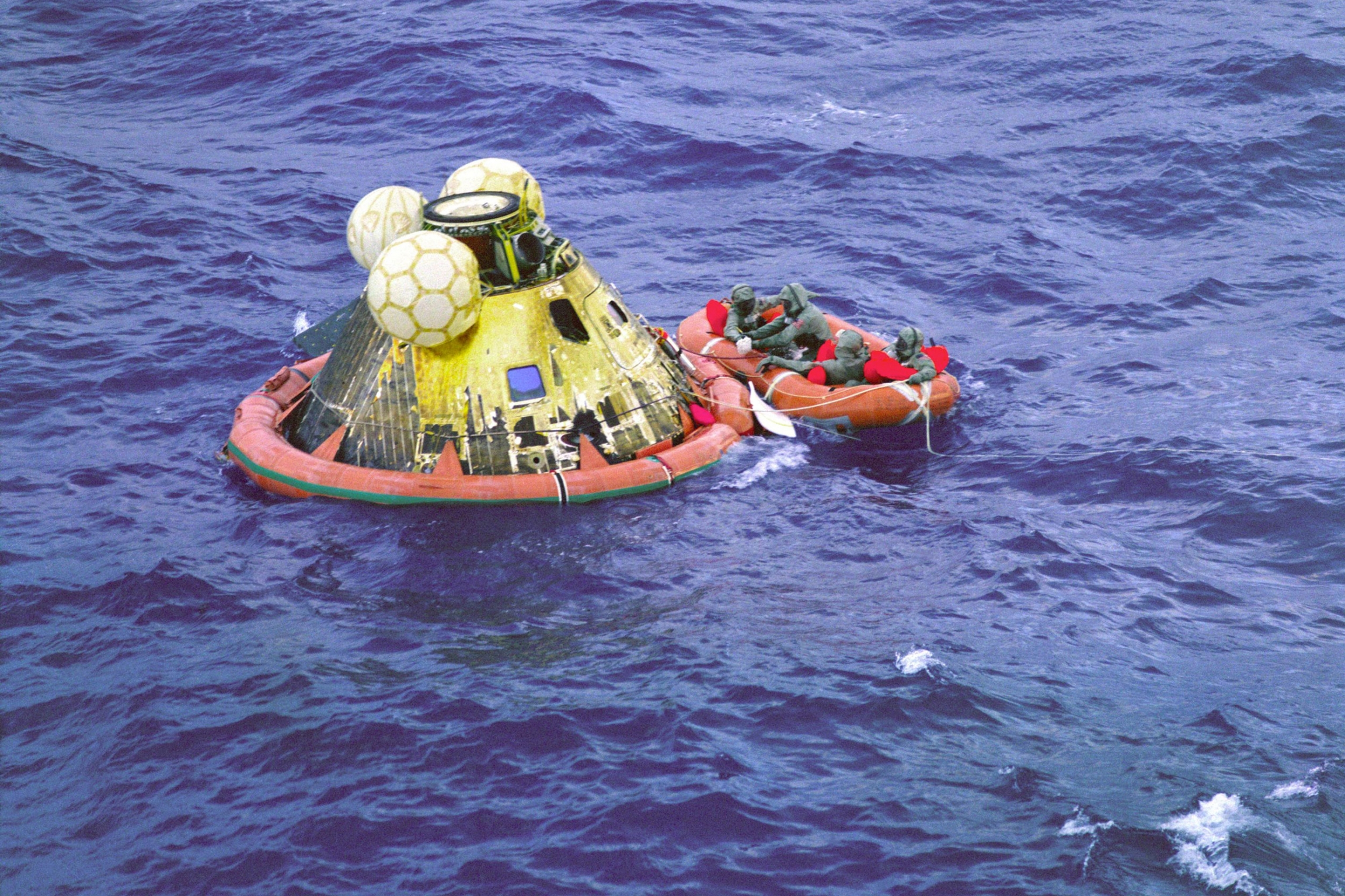 A small orange raft is shown with astaurants aboard, floating next to luna modual.