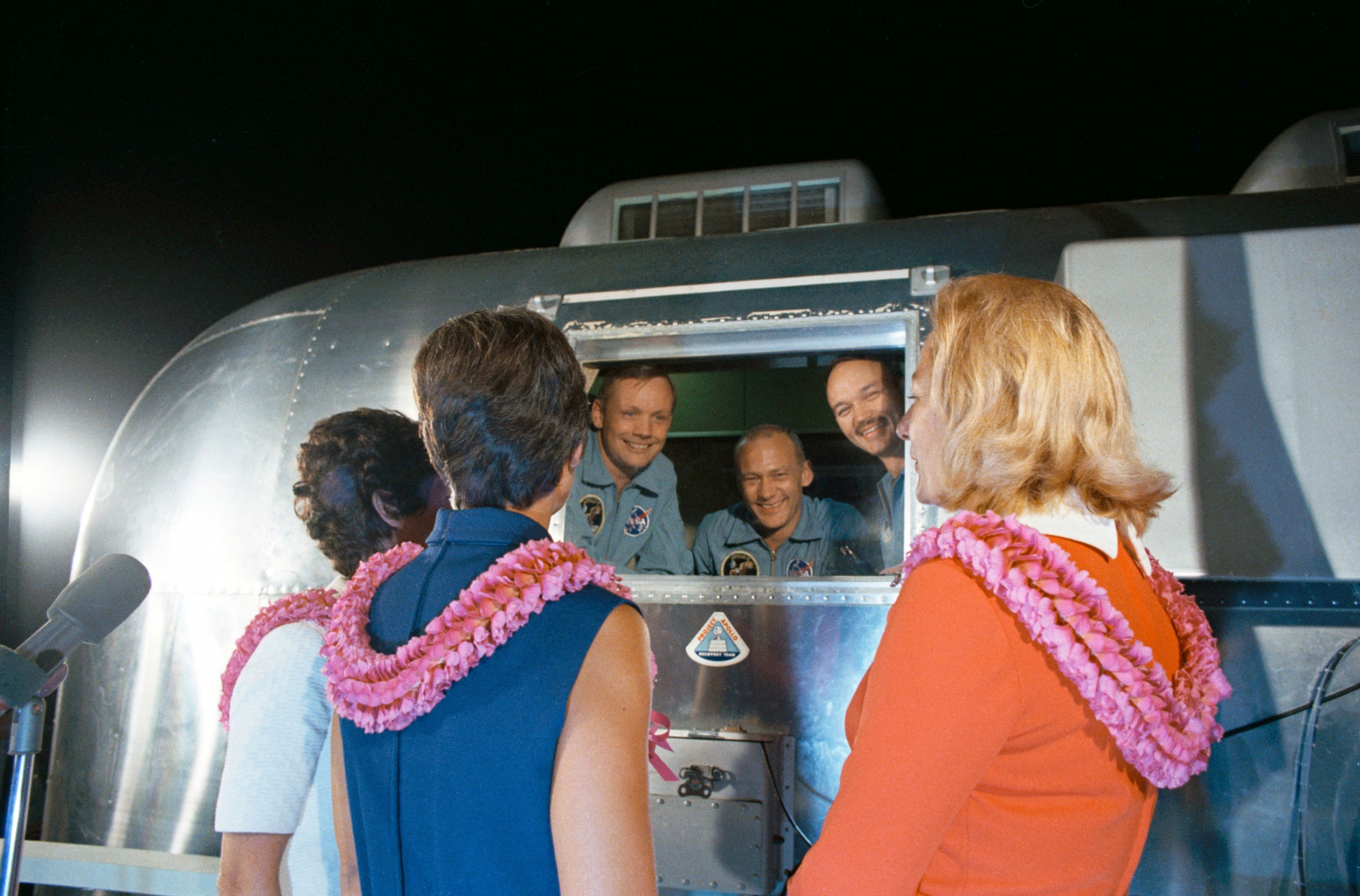 A silver-colored containment structure is shown Neil A. Armstrong, Edwin E. Aldrin Jr., and Michael Collins speaking with their wives.