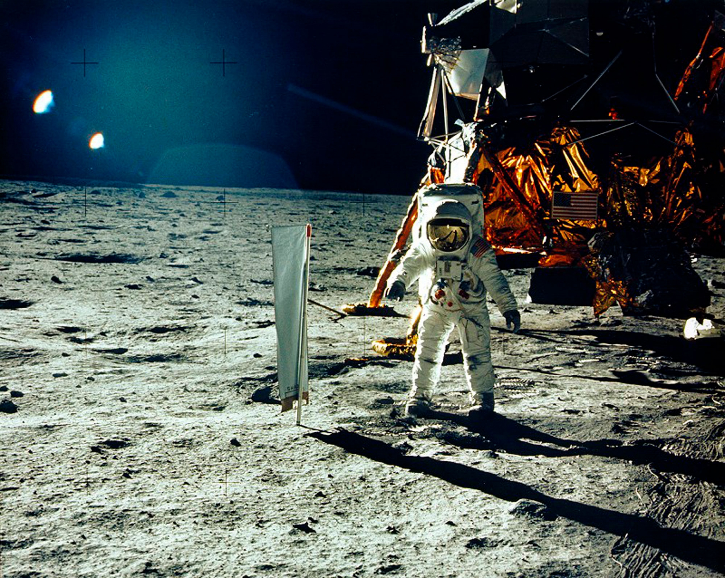 An astraunant is show in full protective gear standing on the surface of the moon.
