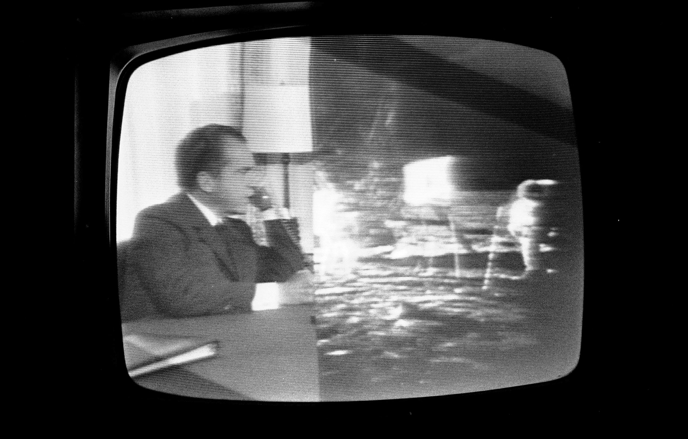 In a photograph of a television,  President Richard Nixon is shown on the left and Apollo 11 crew is shown on the right all in black and white.
