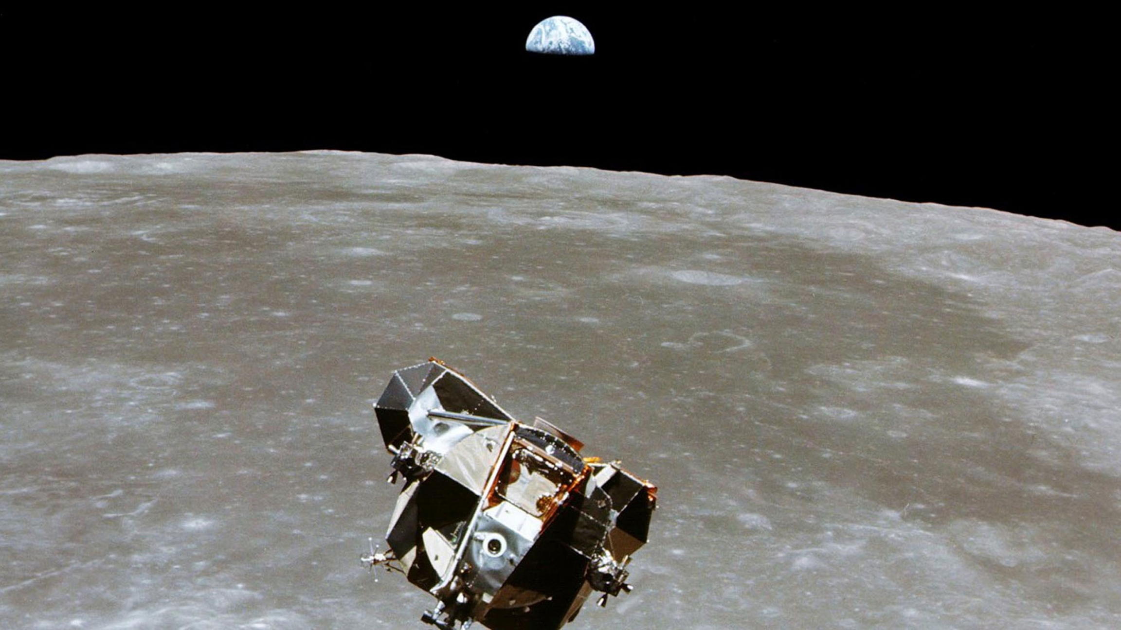 The Apollo 11 Lunar Module is shown in the nearground with the moon's surface below it and Earth shown in the distance.