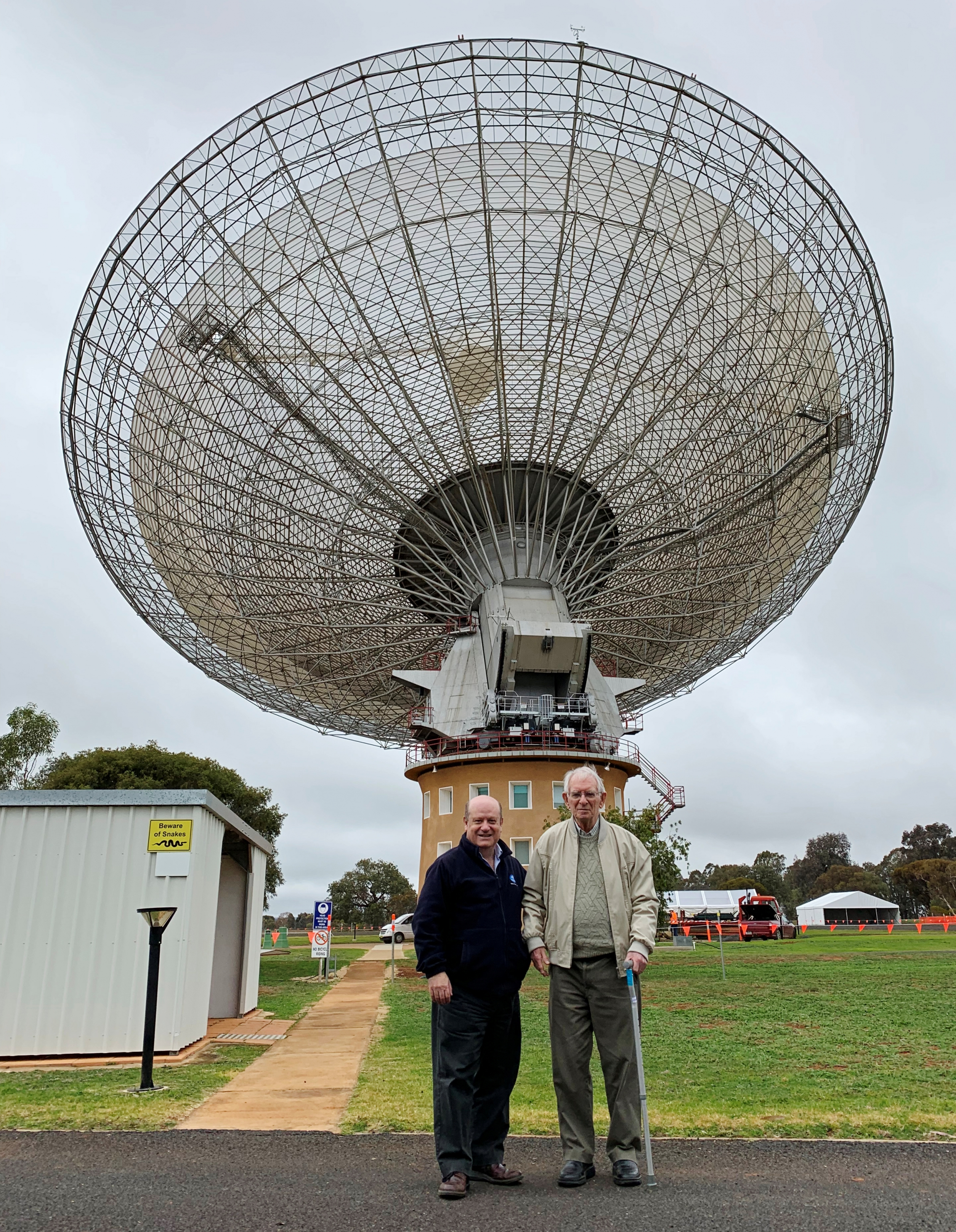 two men stand in front of an observatory