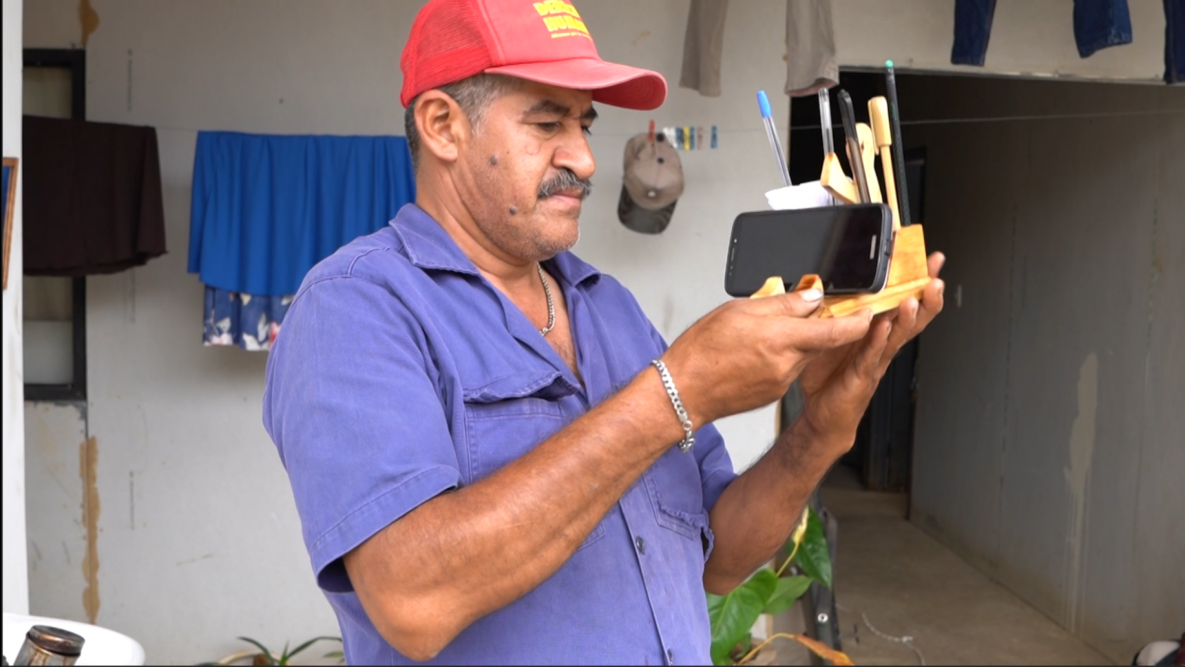 A man shows his pencil holder creation