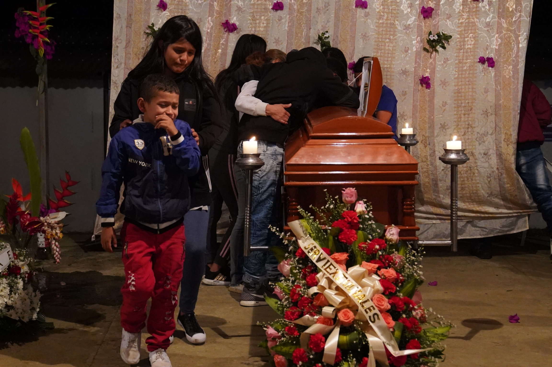 Family mourns and weeps over a coffin