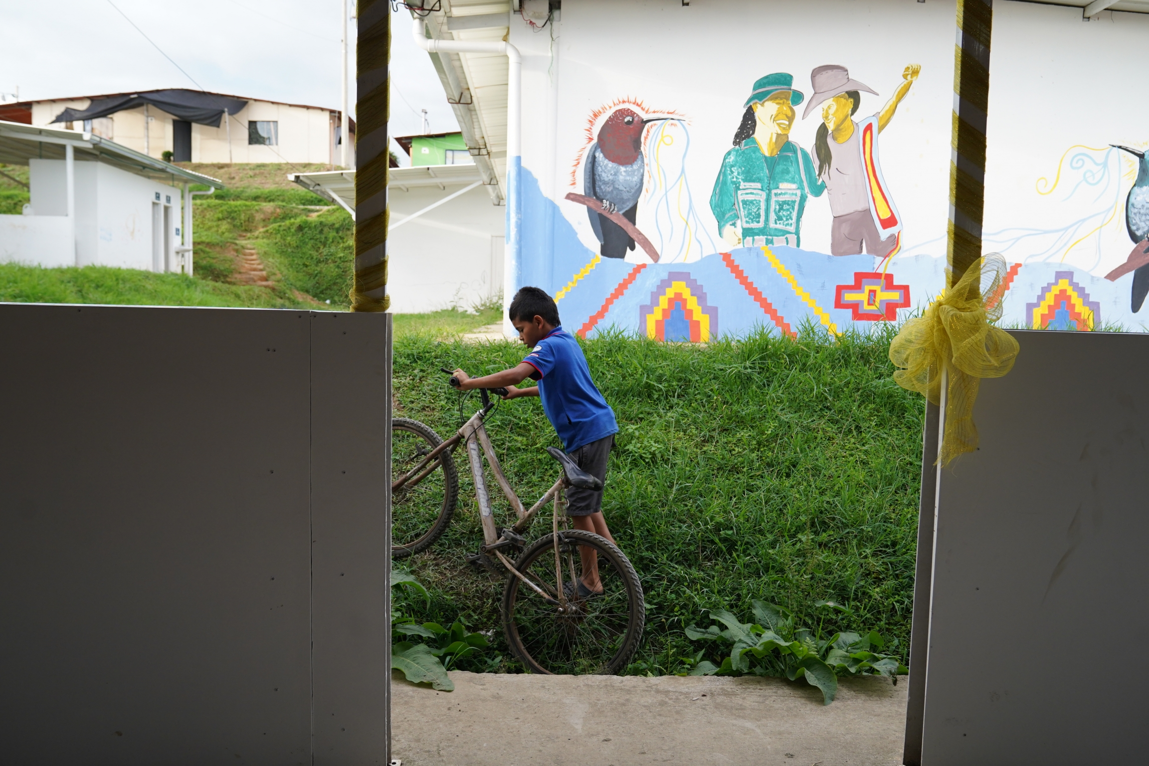 A boy rides his bike seen through a window near wall with mural