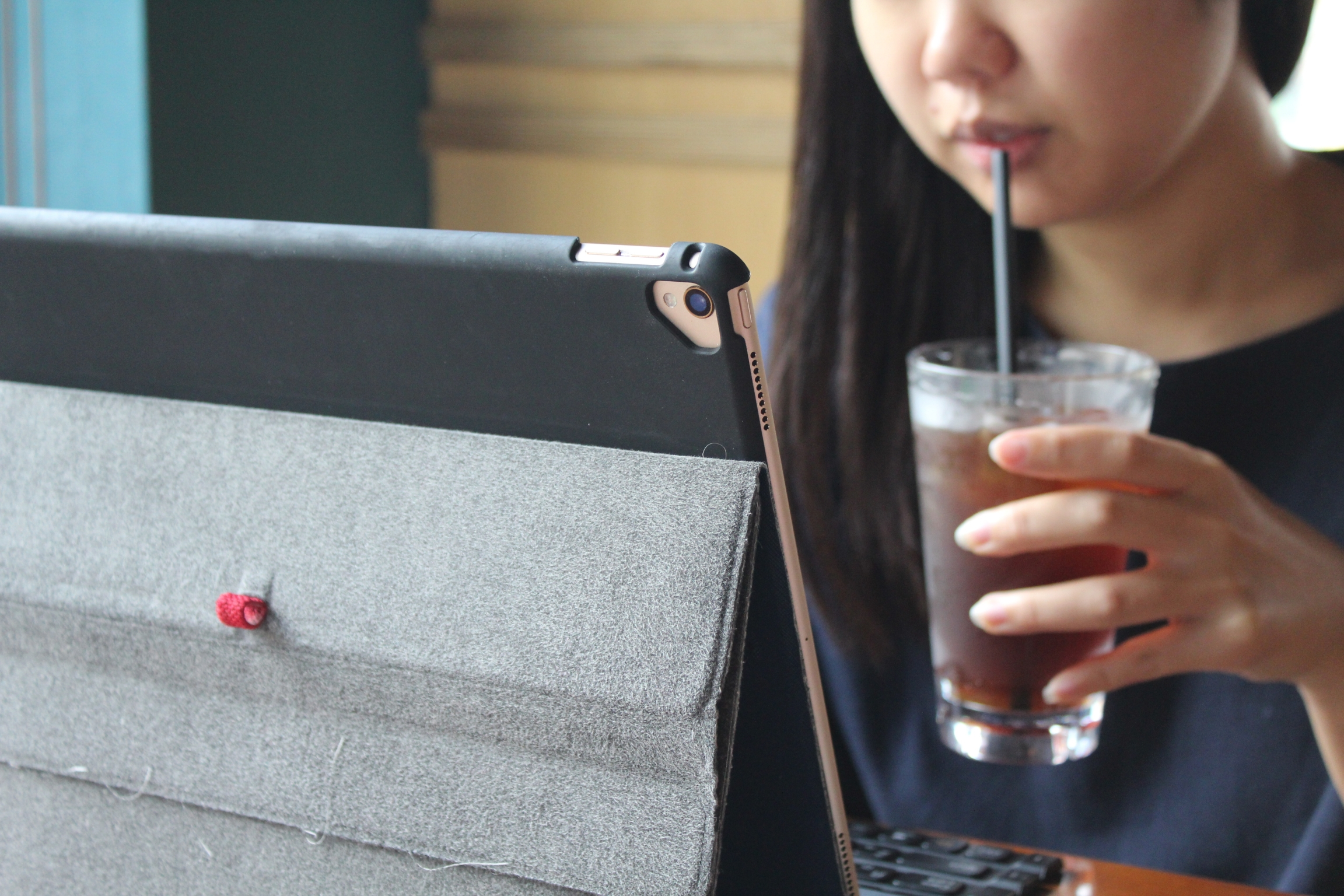 A woman sips a cold drink while looking at her laptop screen