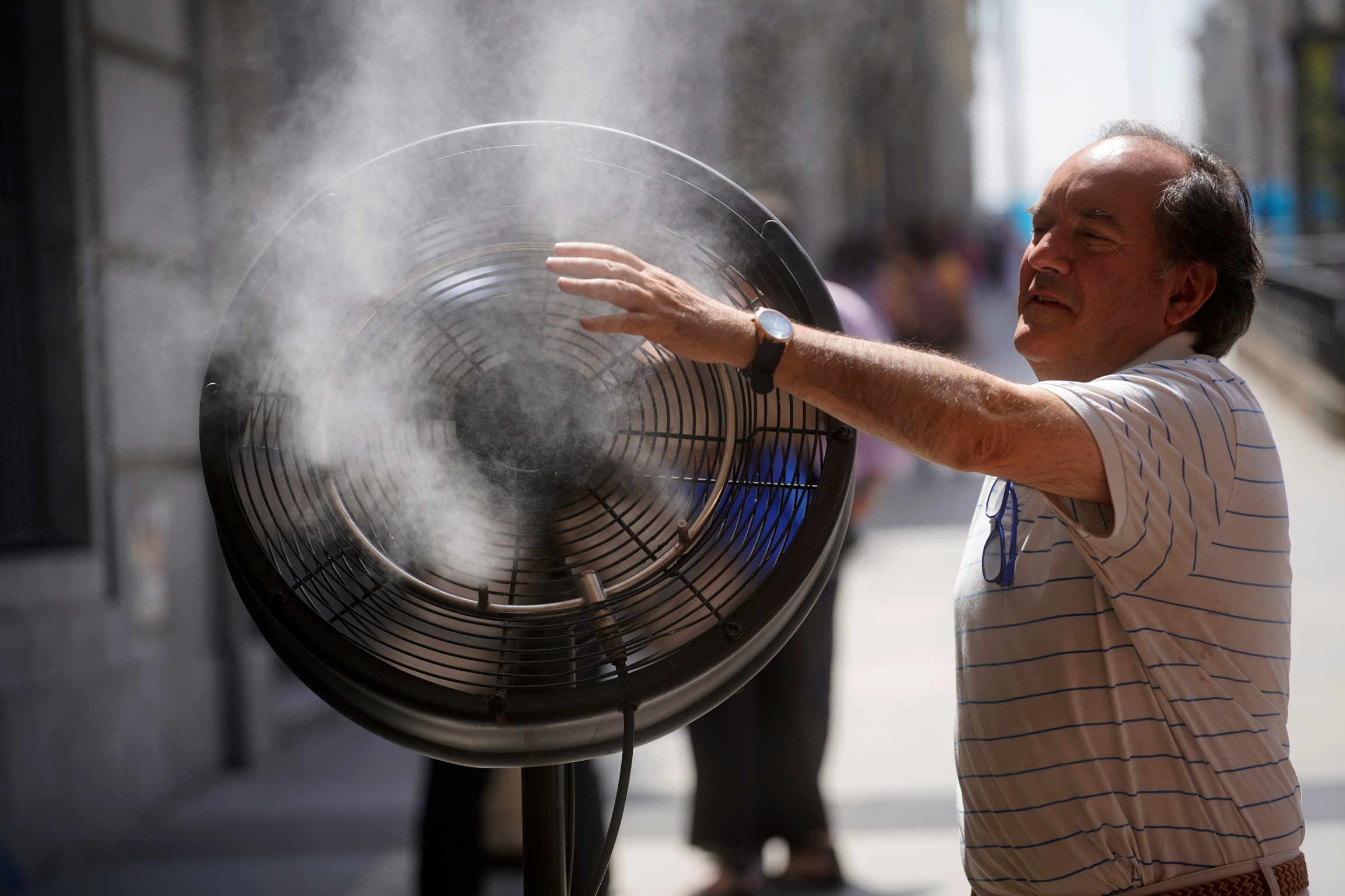 Man cools himself down with huge fan and water splash