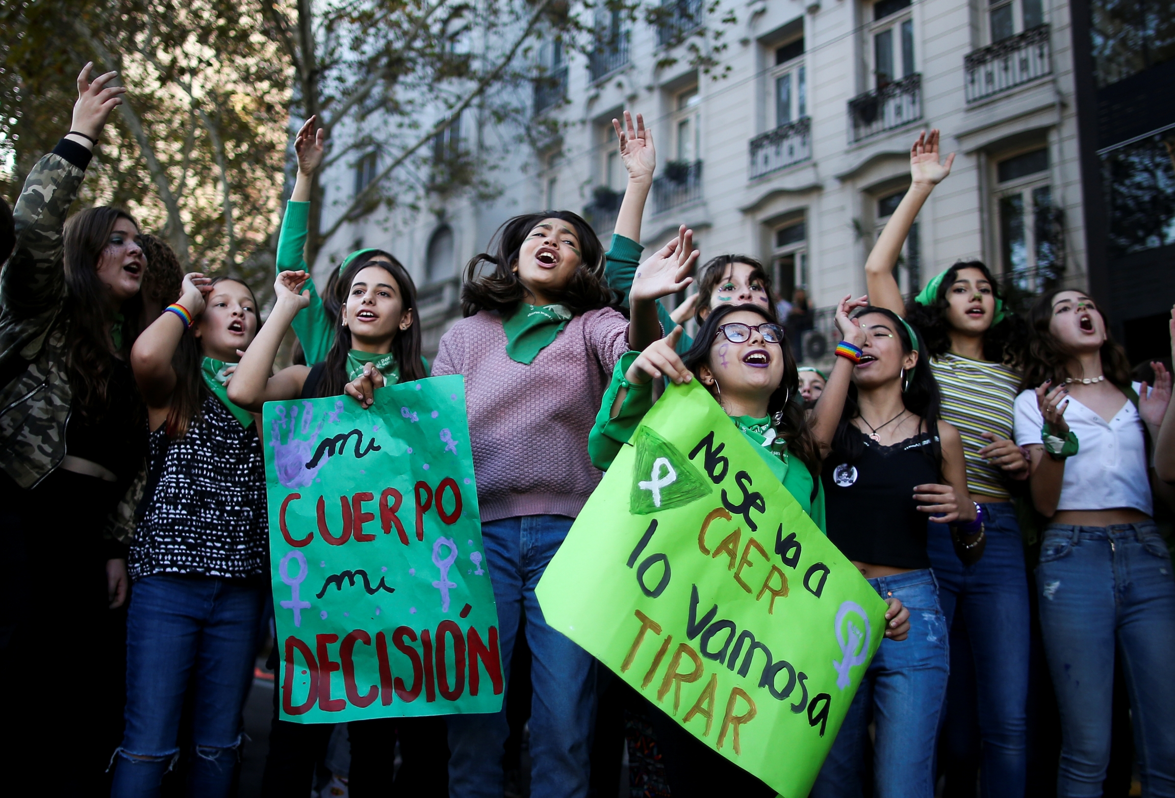 Women stand together and hold sings in Spanish in a city.