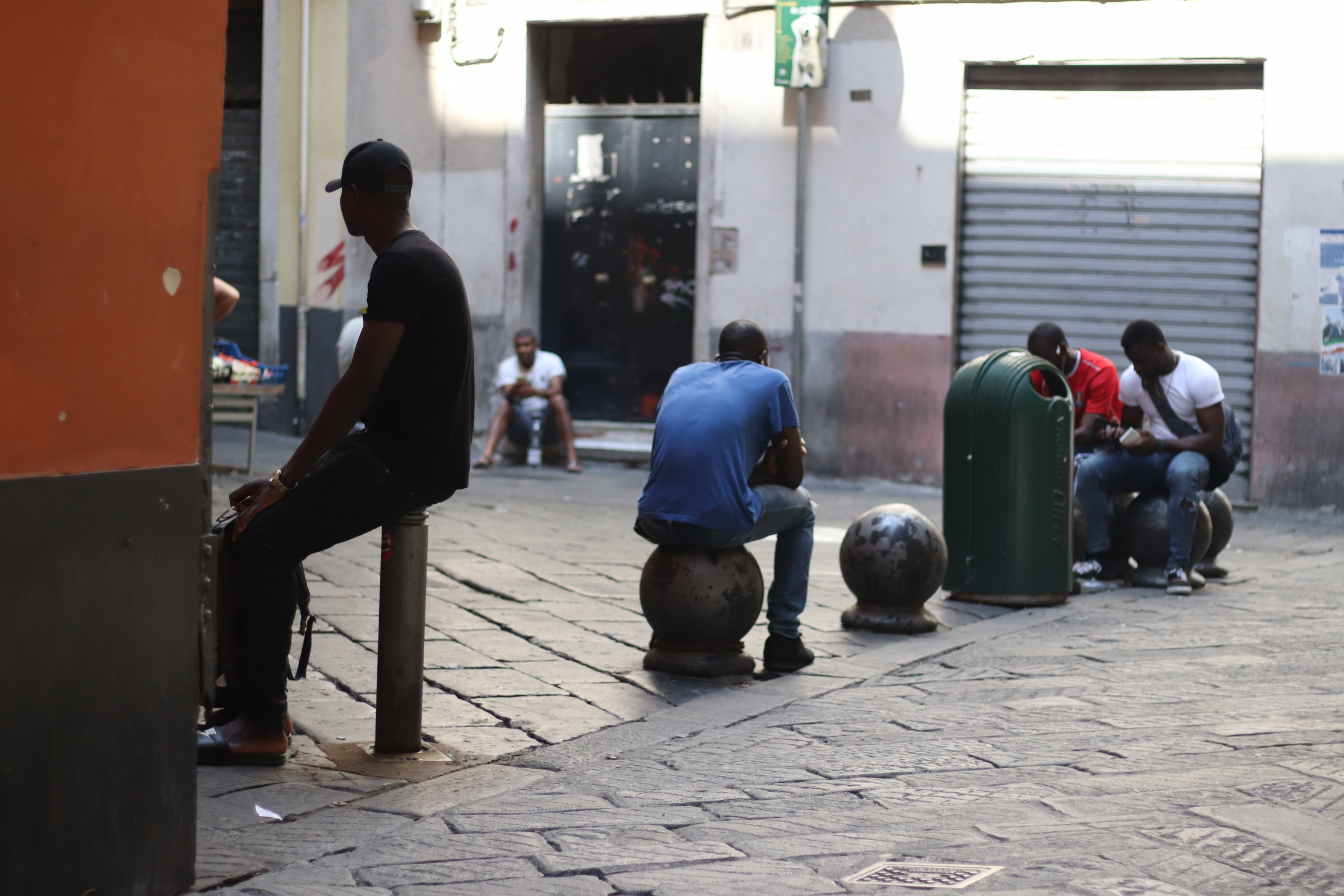 asylum-seekers sit in the street idly