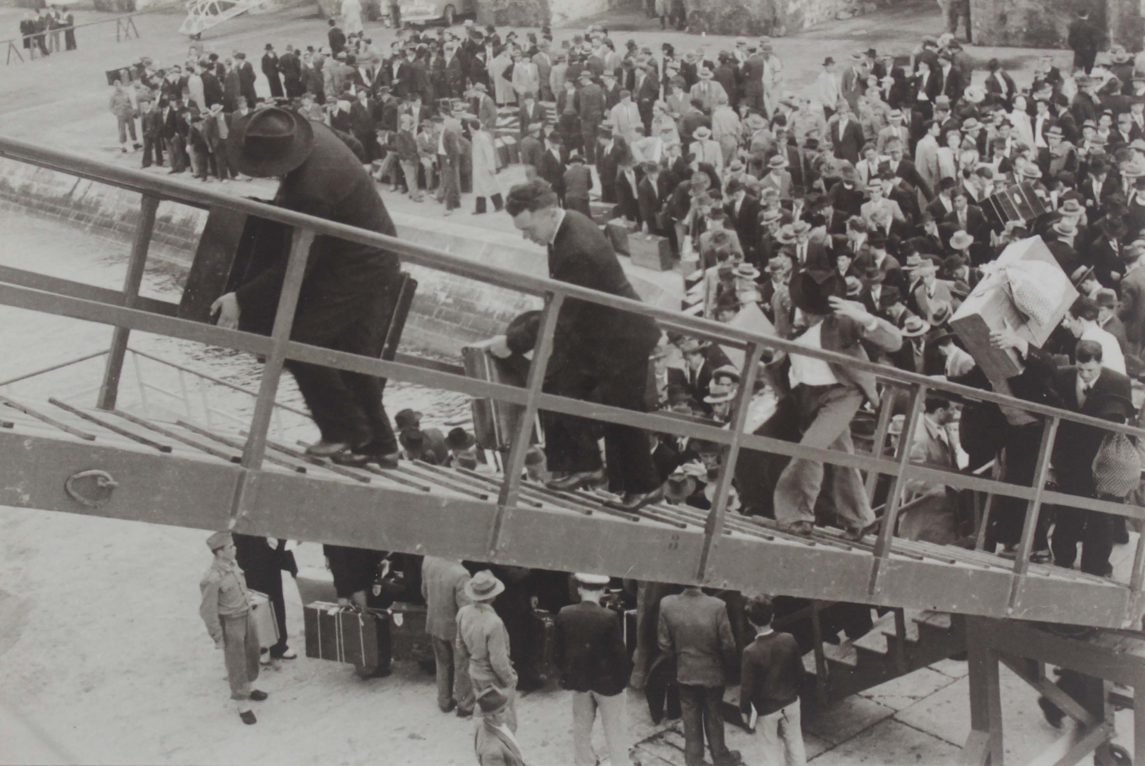 A black and white photo of men ascending to a ship, with others on the quay below
