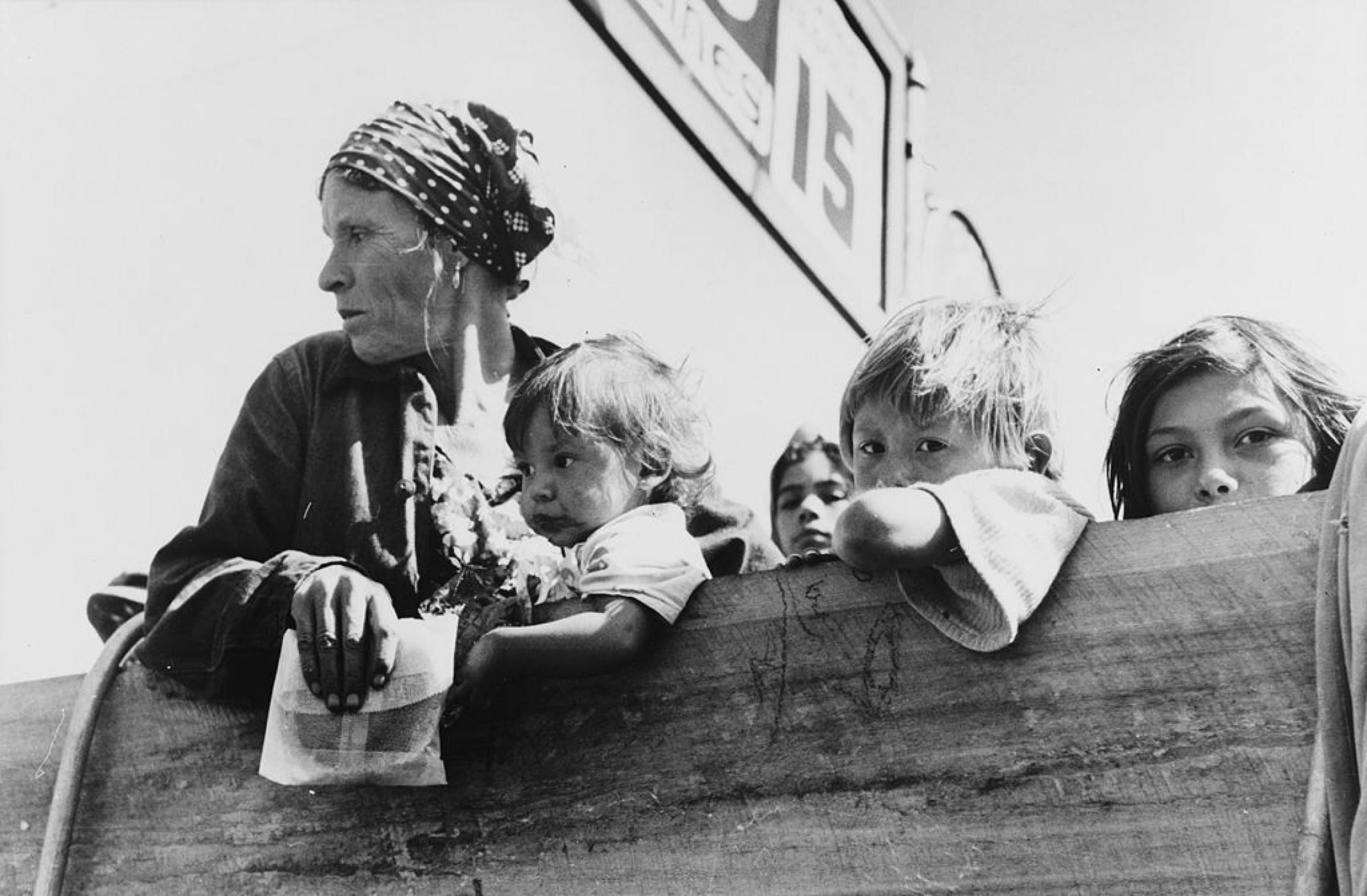Mexican woman and children looking over side of truck