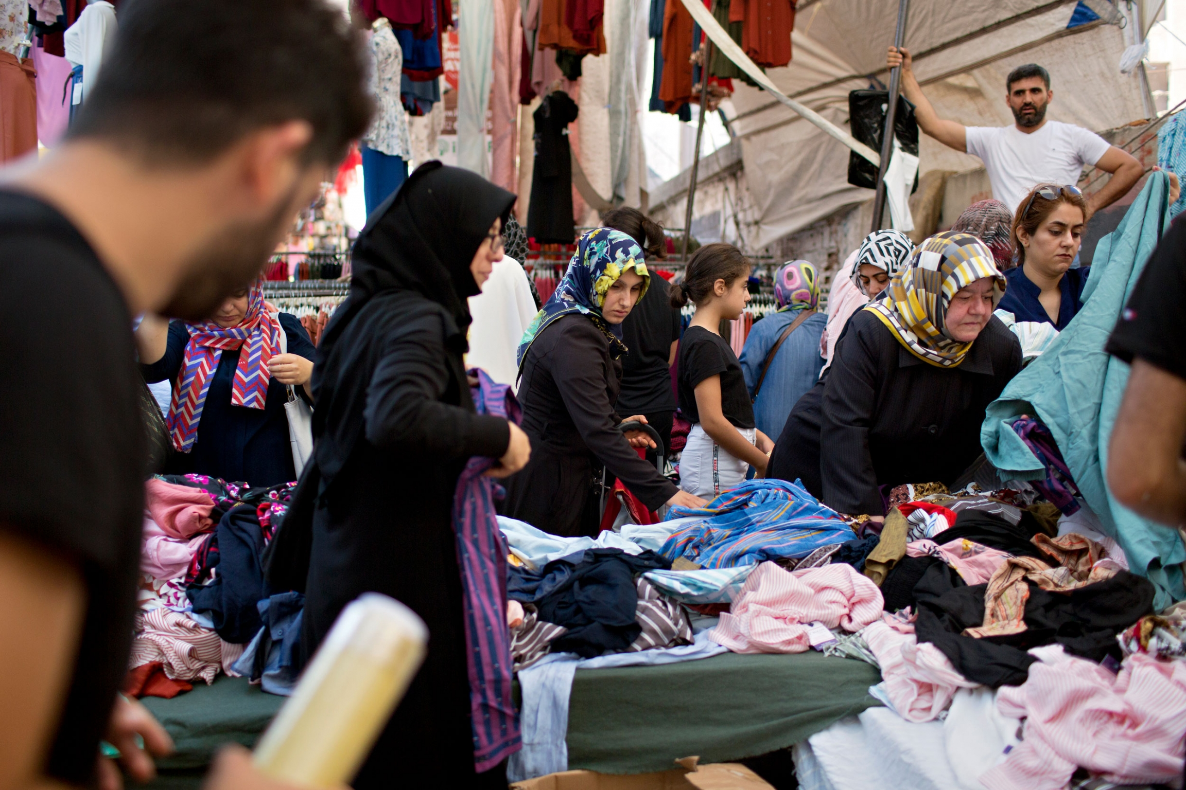 Several women wearing head shalls are show shopping at a market.