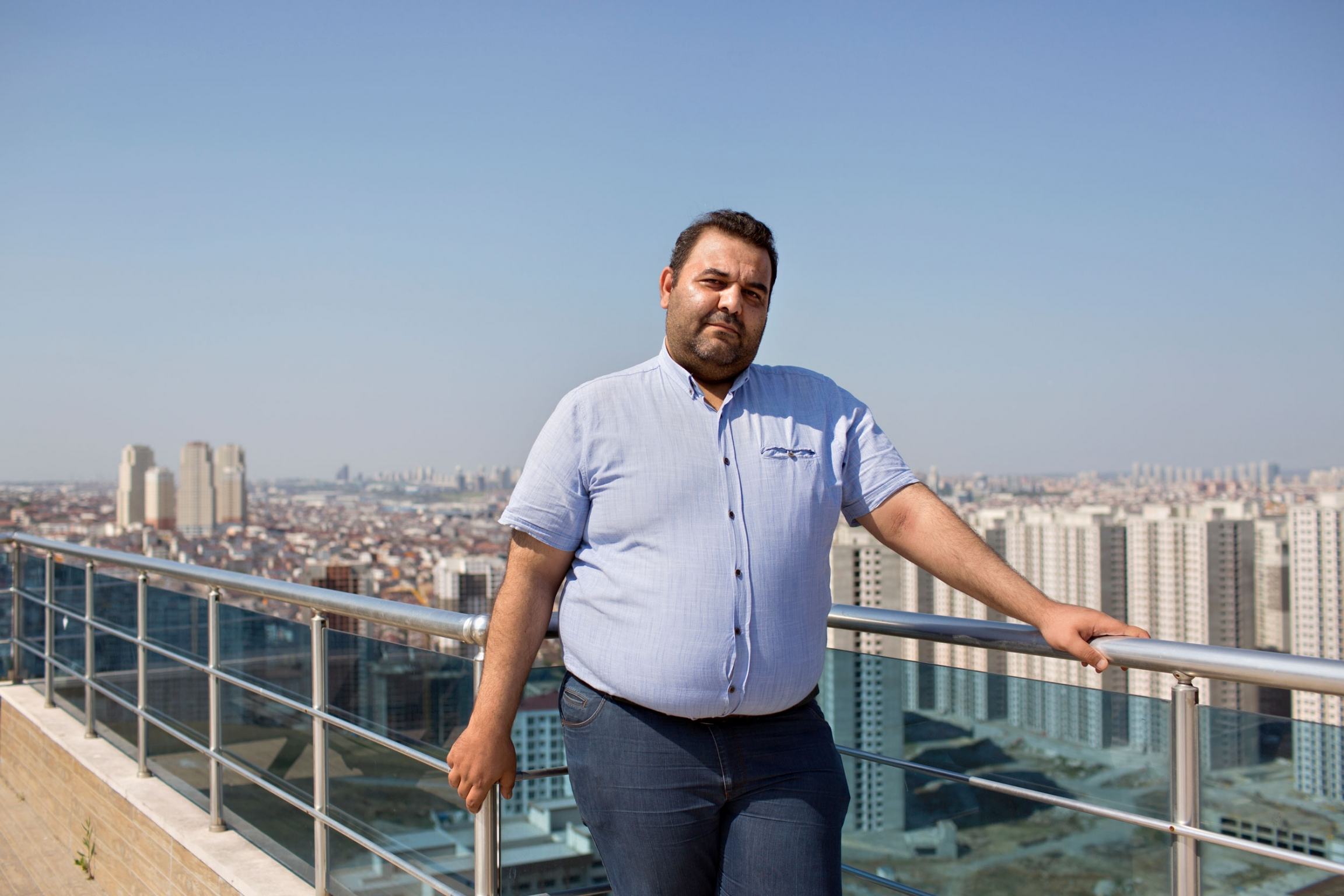 A man is shown in a blue button down shirt and jeans leaning against the railing of a rooftop deck.