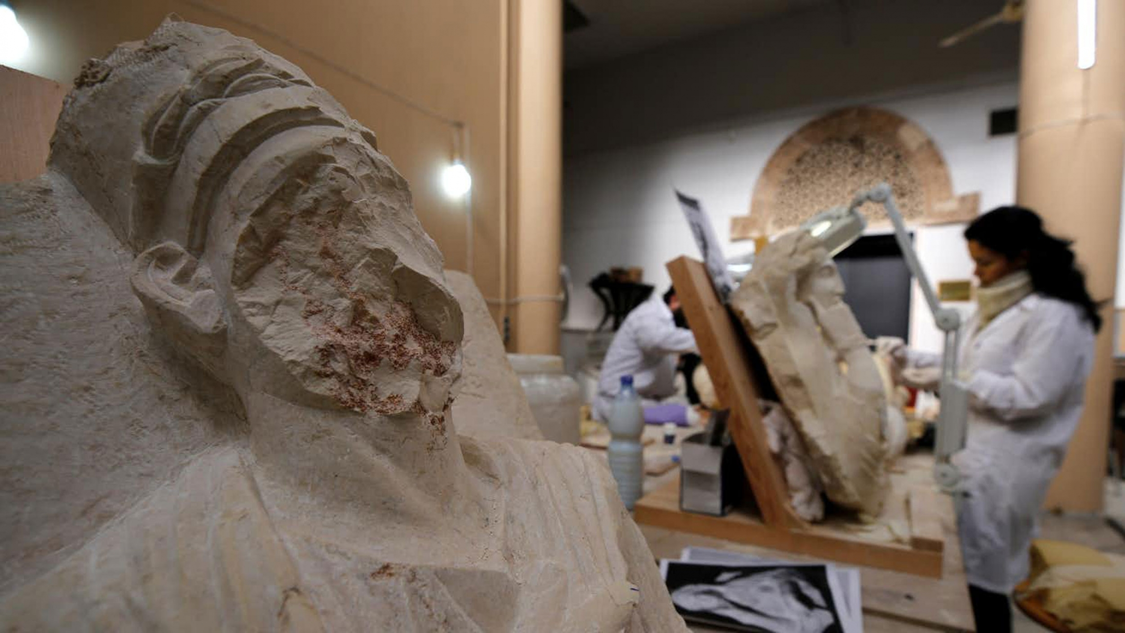 A woman works on damaged statues - one is missing part of its face - from Palmyra at Syria's National Museum of Damascus