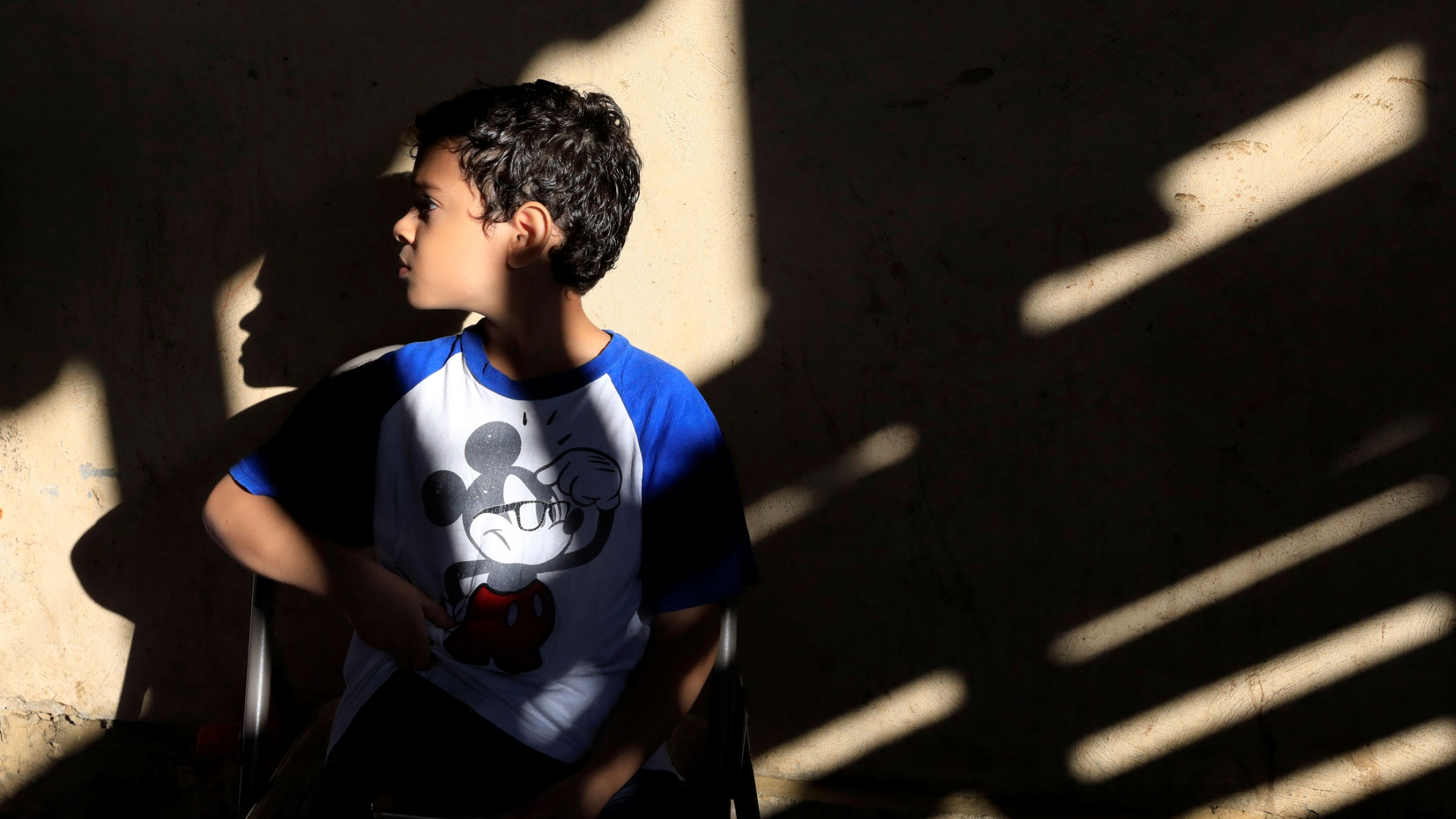 A young child is shown looking to his right and wearing a blue and white Mickey Mouse shirt.