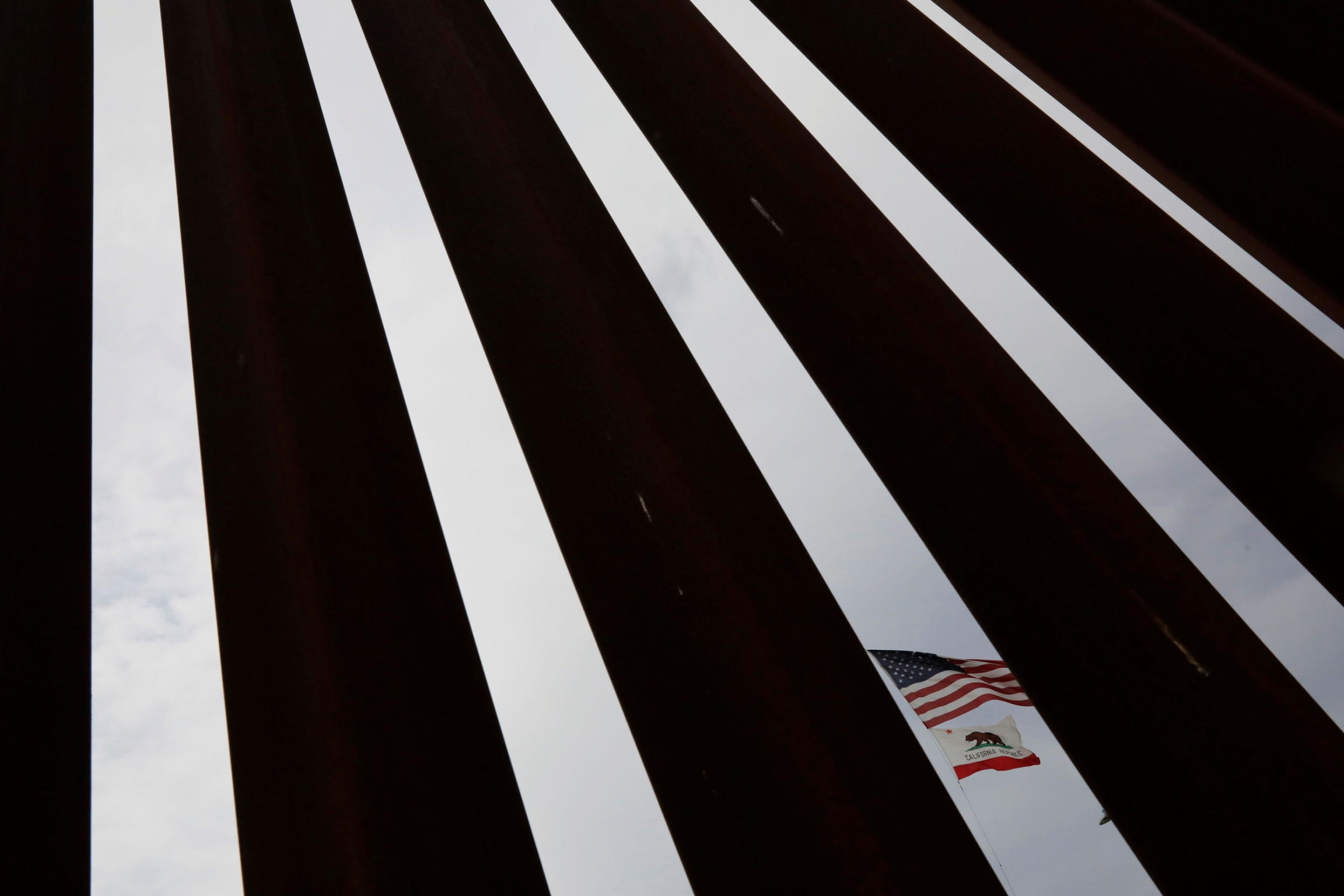 A photograph with dark metal slats are shown in contrast to the blue sky in-between with the US and California flags in one of the slots.