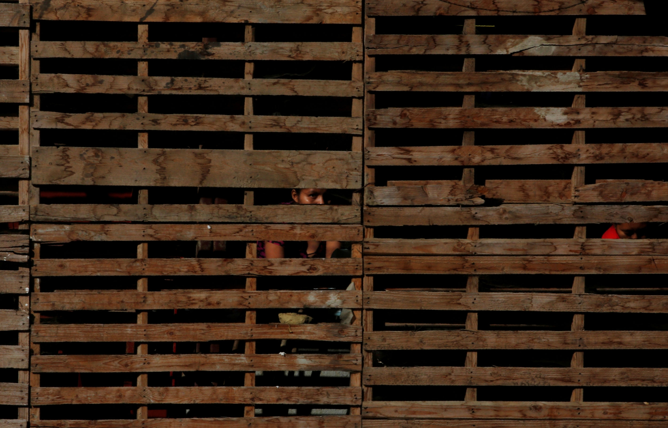 Horizontal wooden slats are shown across the entire photograph with the face of a woman in shadown.