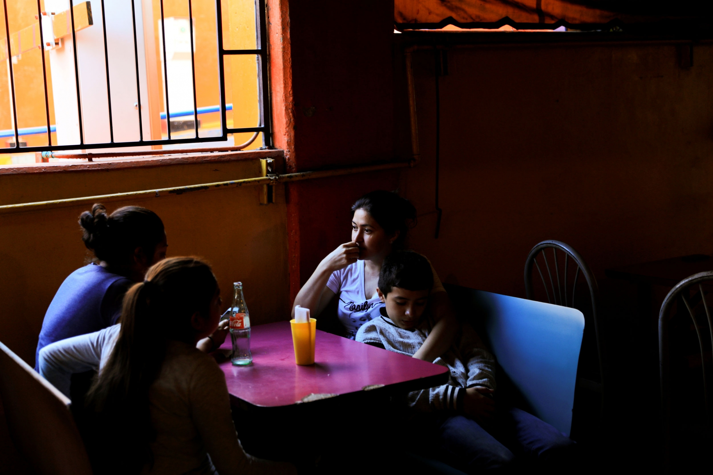 Three women are shown sitting around a table along with a teenage boy shown by the light of a window from above.