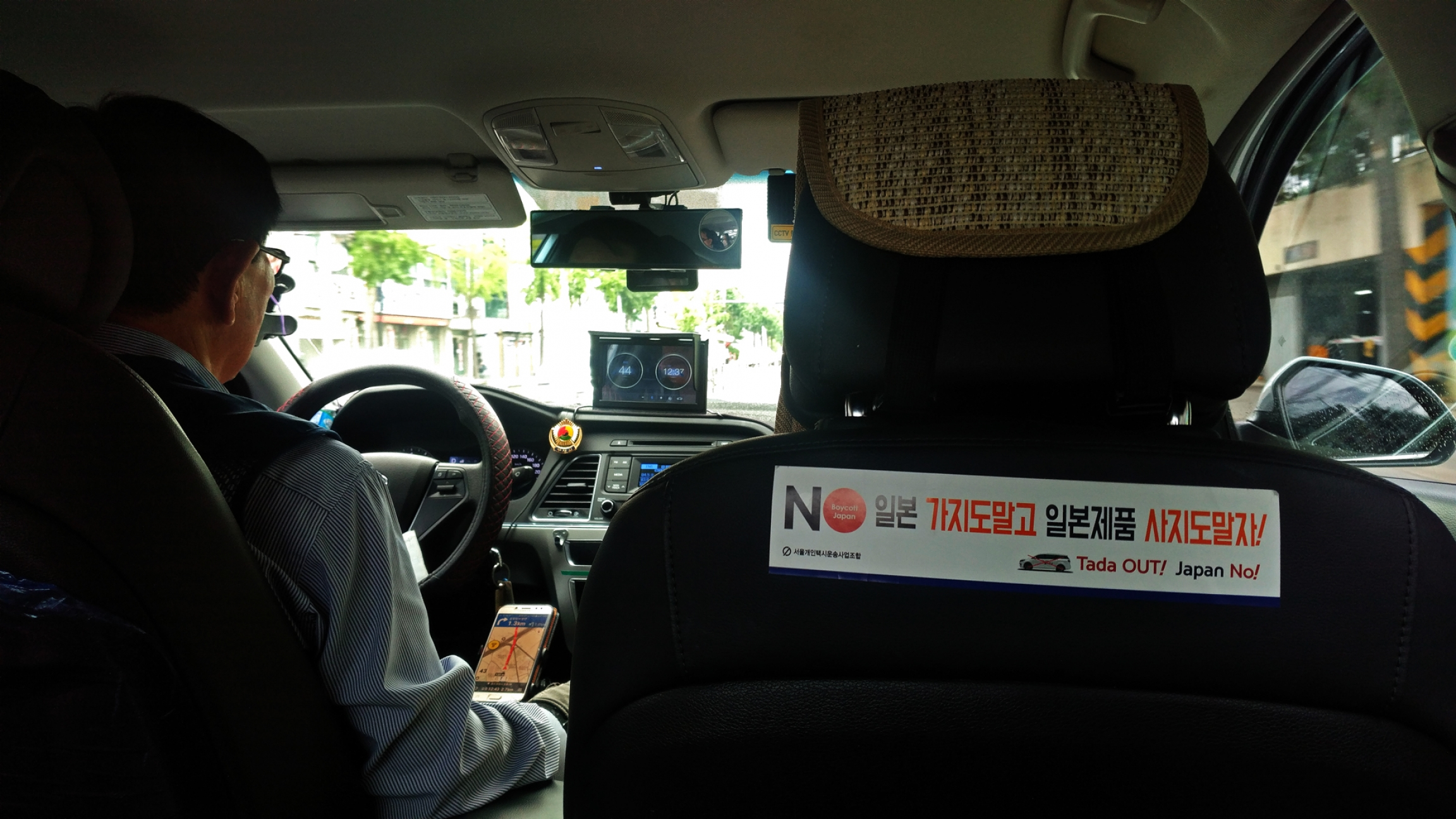 A taxi interior features an anti-Japan sticker
