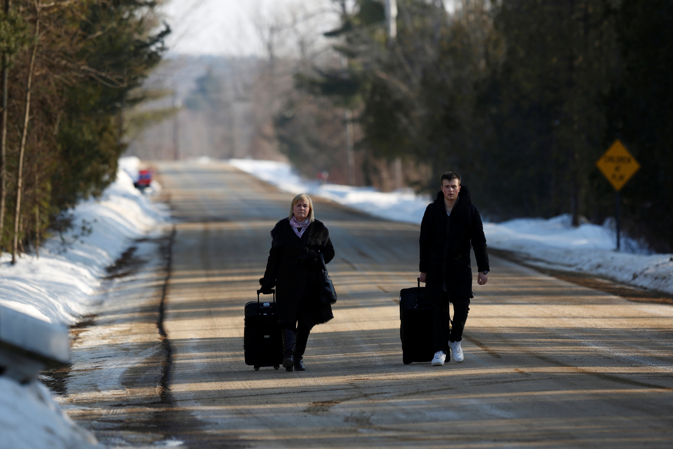Two people walk with luggage along an empty road