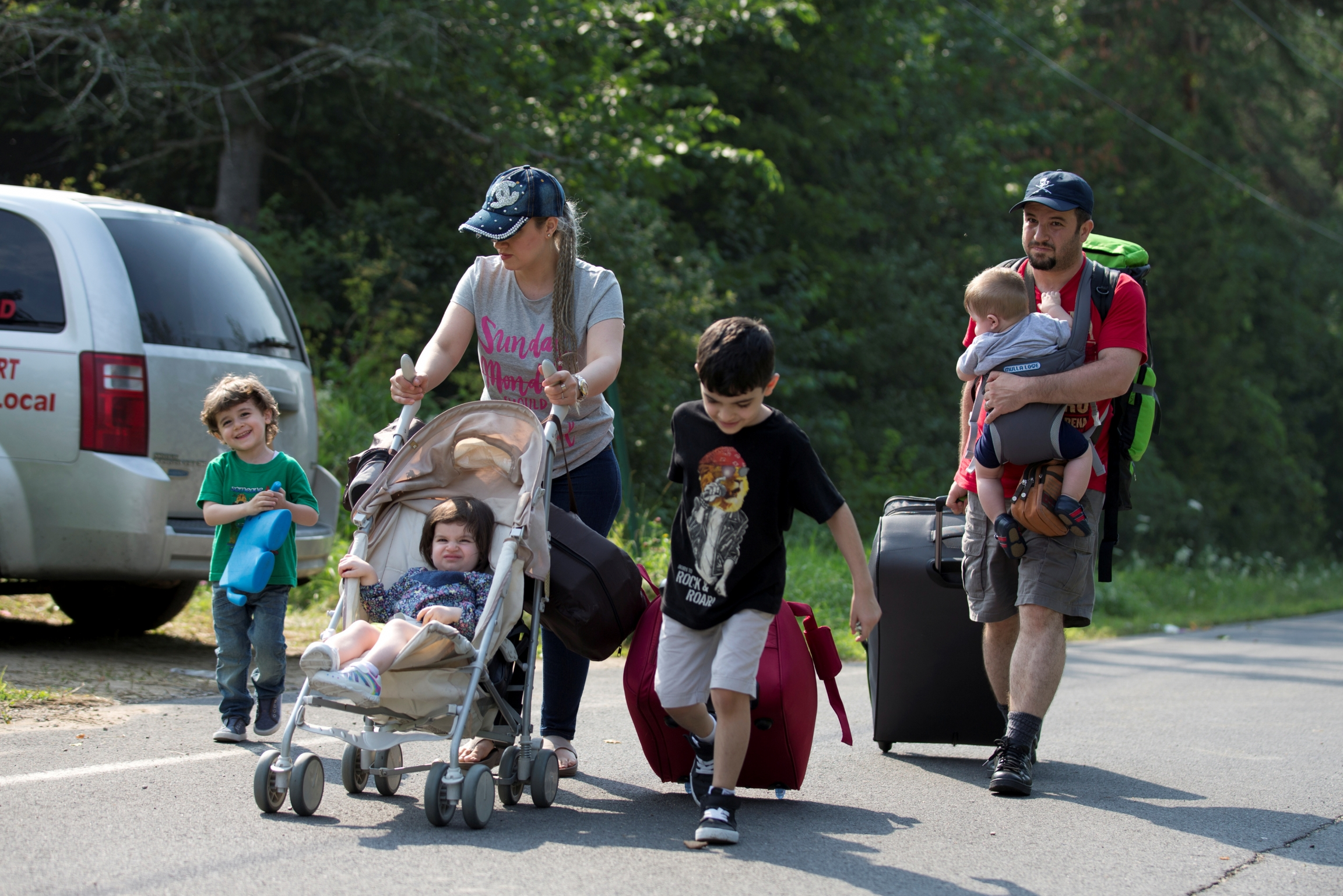 A family of four pushes stroller across a road