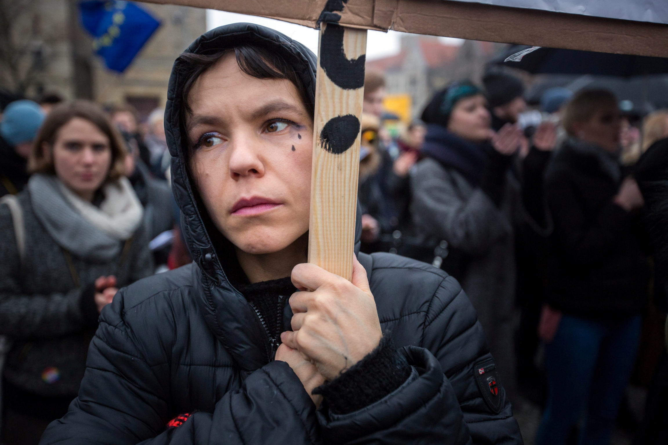 A woman protests against abortion restrictions carrying sign with tear drops painted on her face