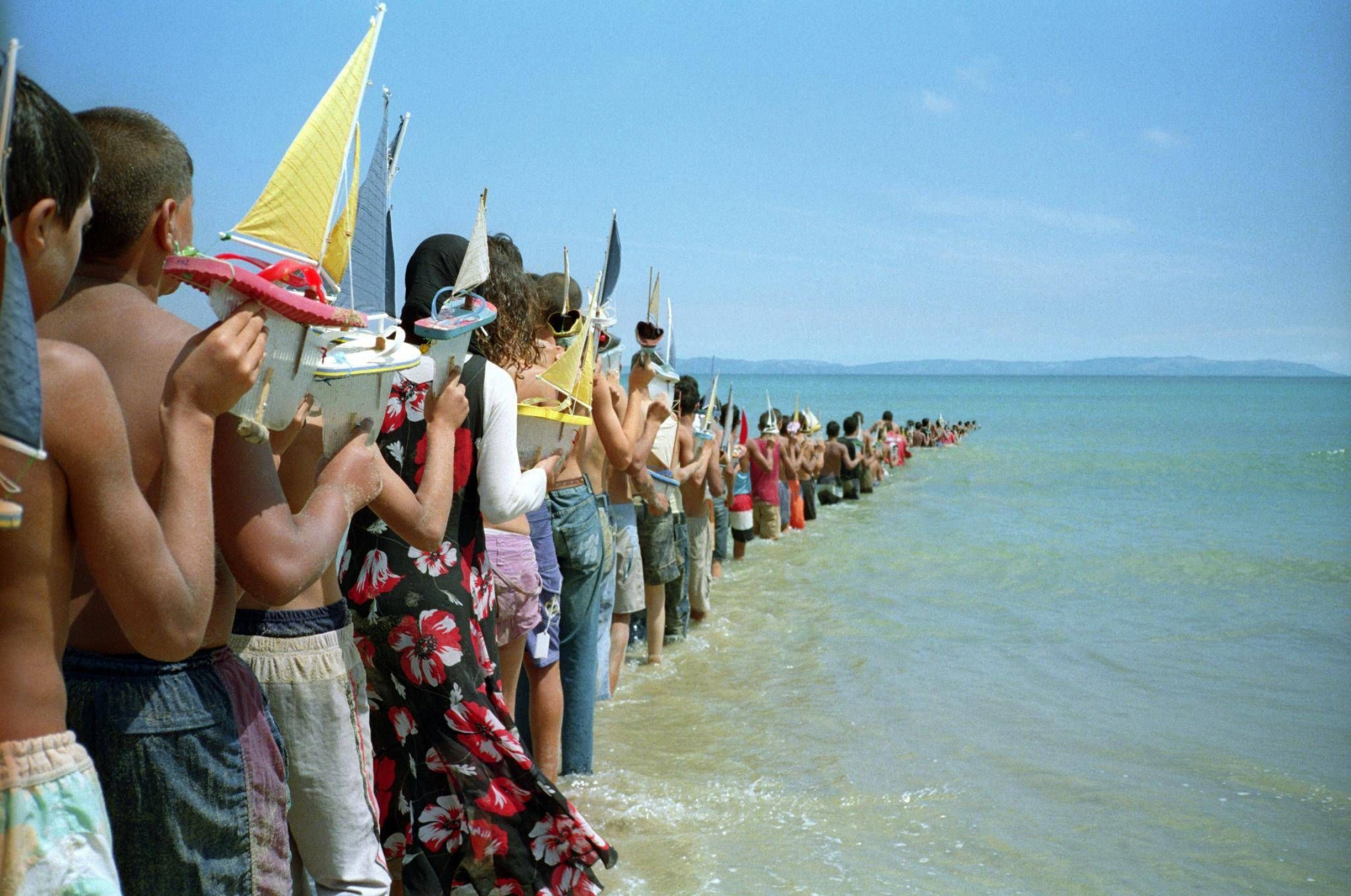 A line of people holding toy boats is seen going into the ocean.