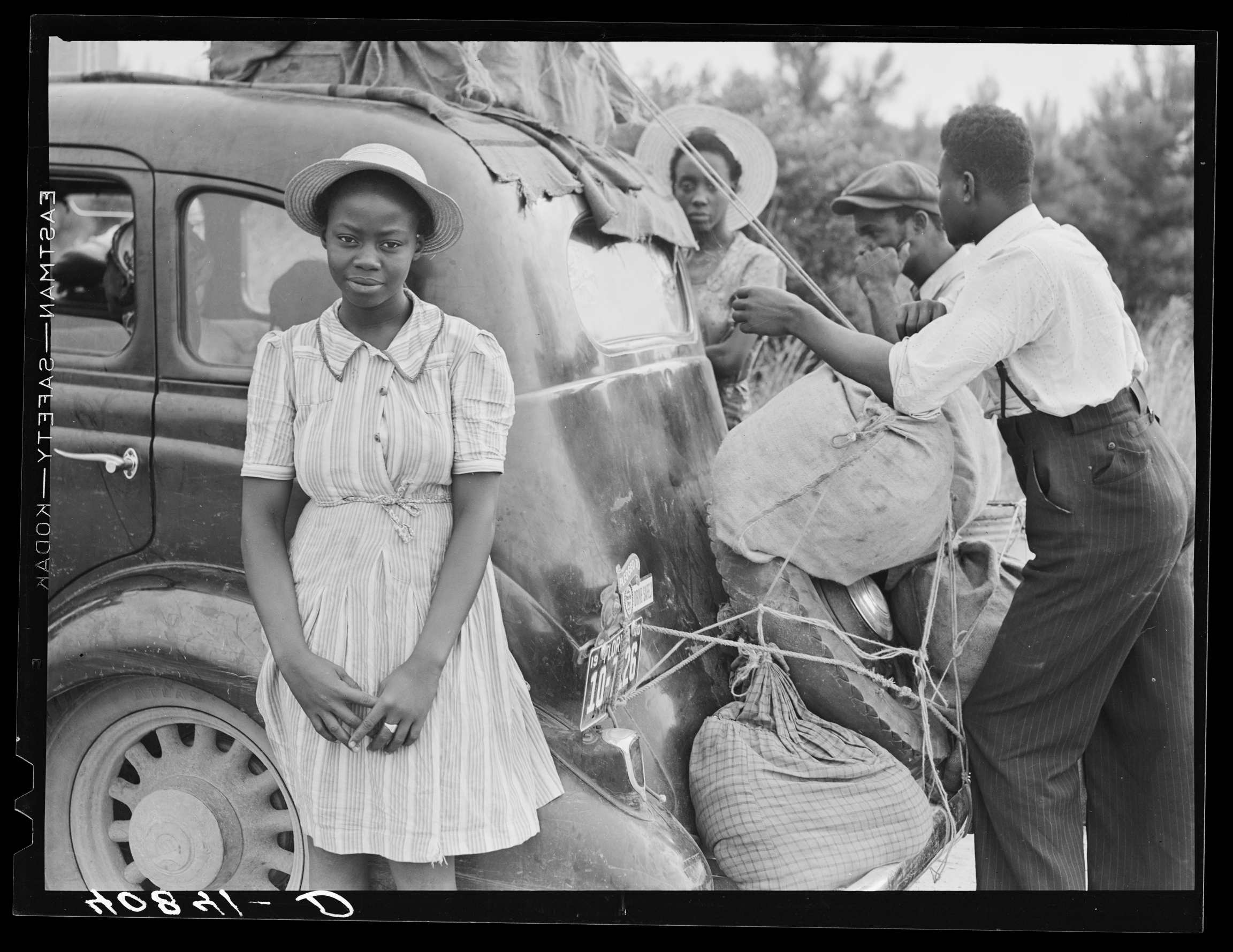 A family is seen tying sacks of potatoes to a car.