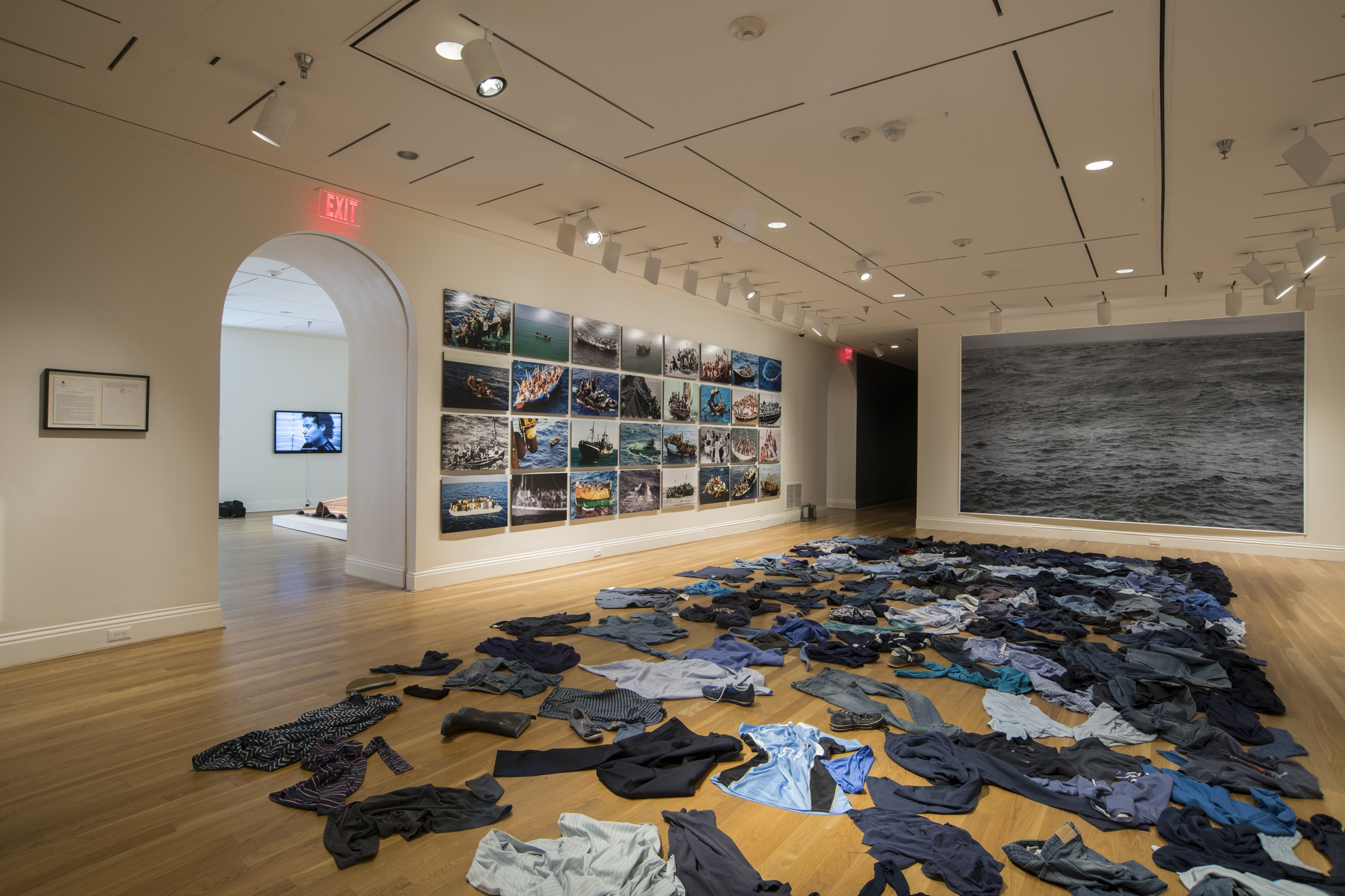 Dark colored clothes are strewn on the floor in an art exhibition.