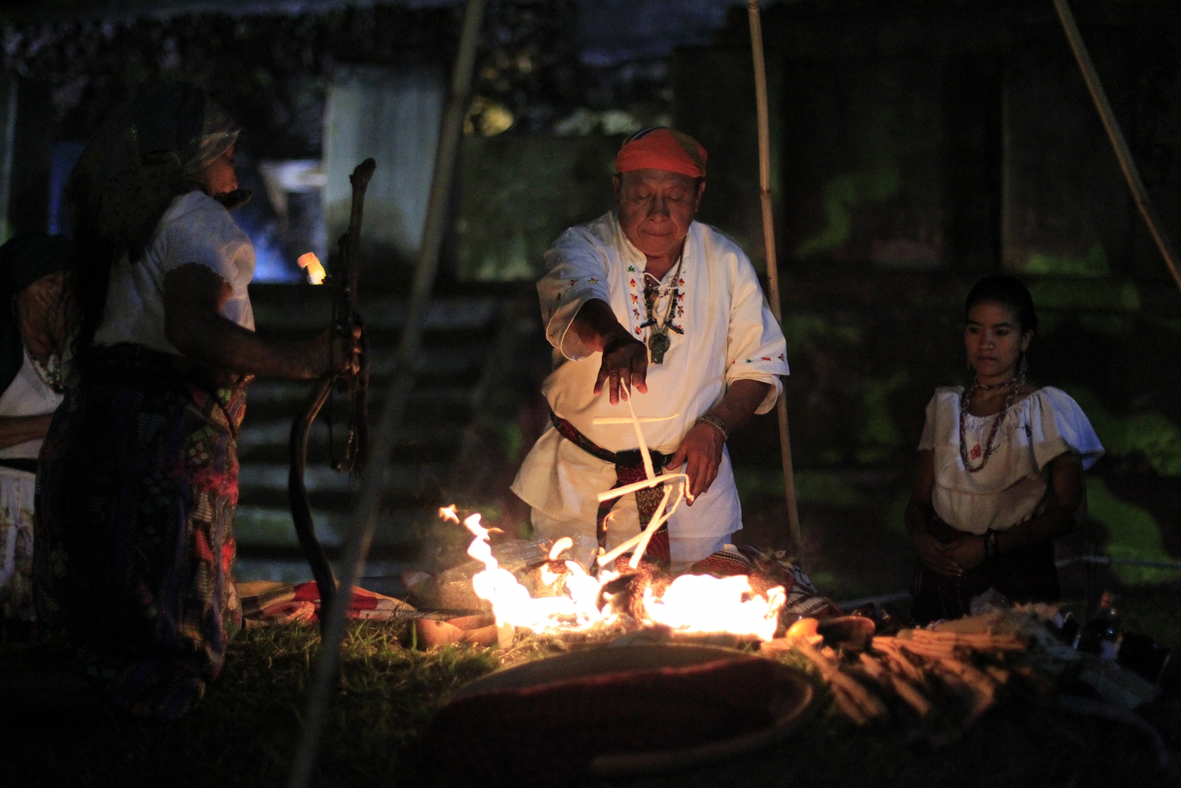 Mayans perform a fire ceremony at an archaeological site.