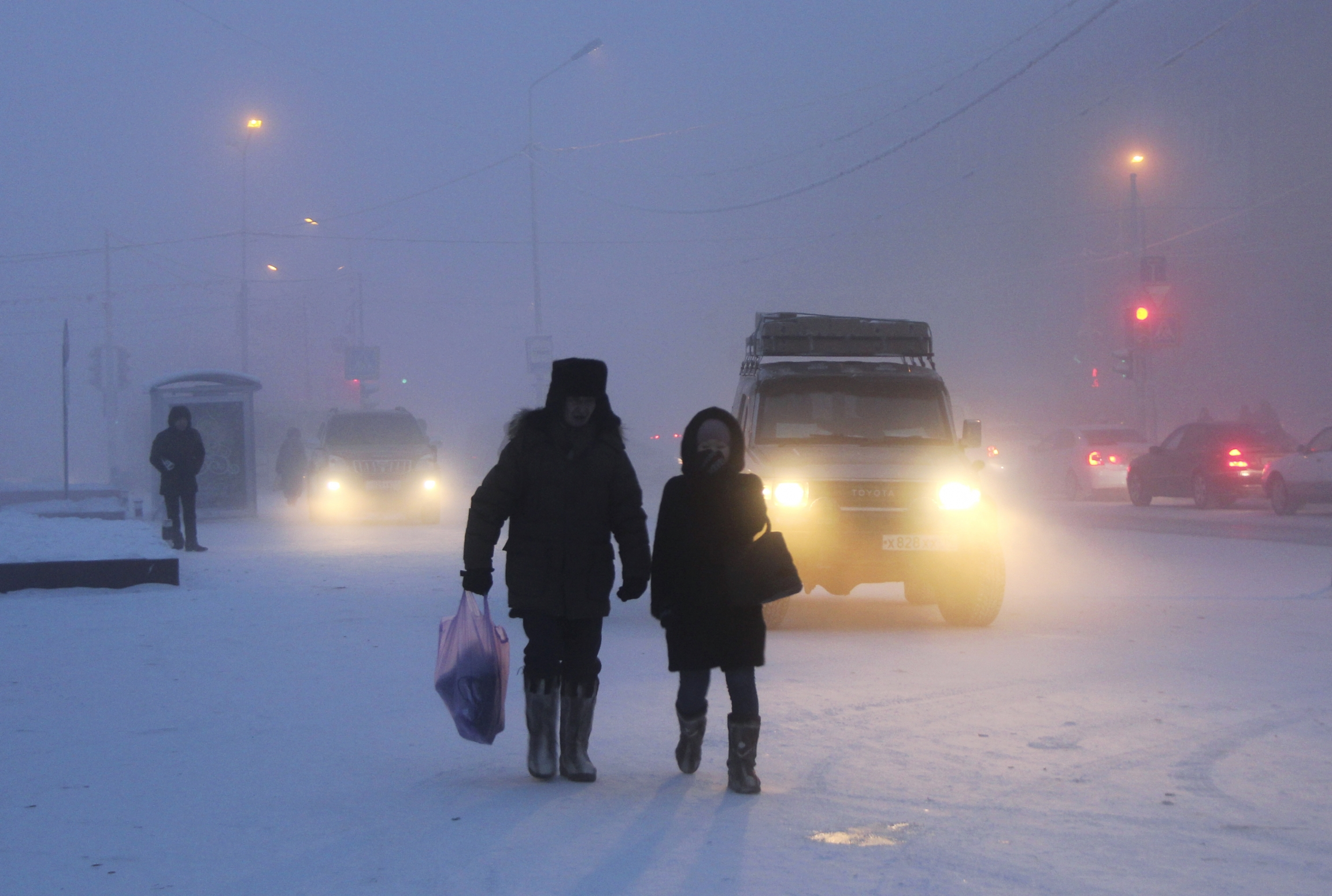 Two people walk in a snowy street scene.