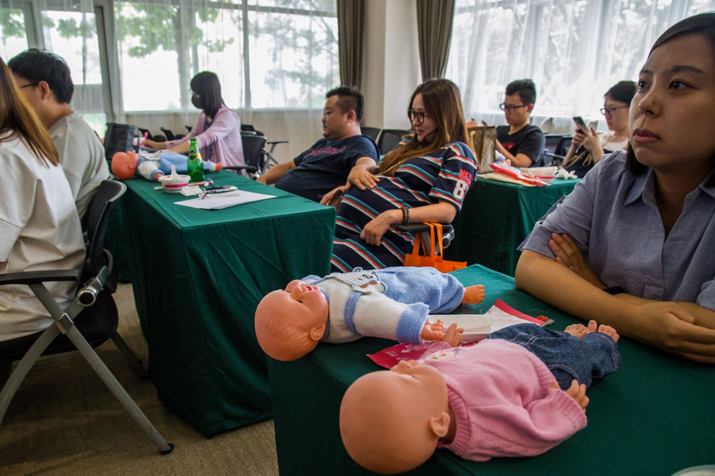 A visibly pregnant woman sits in a parenting class with dolls on the table.