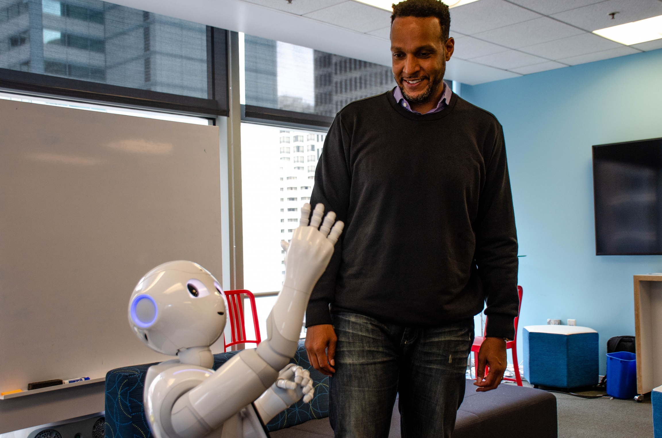 "Softbank Robotics' Kass Dawson, who stands 6'5"" interacts with Pepper, the robot. Dawson says Pepper was designed to be four-feet-tall to make it more ""approachable."""