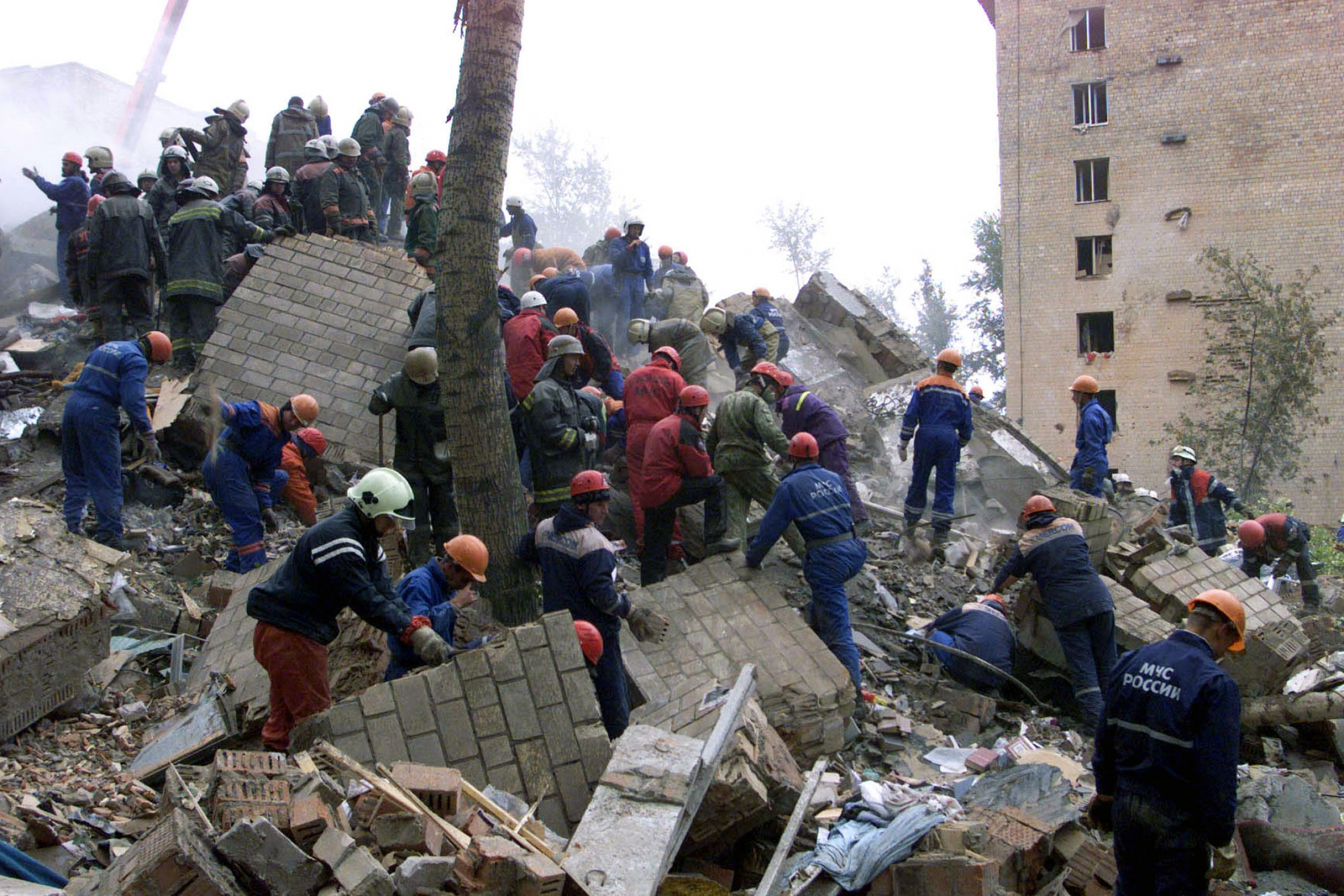 A crowd of people wearing hard hats shift through the rubble of a building