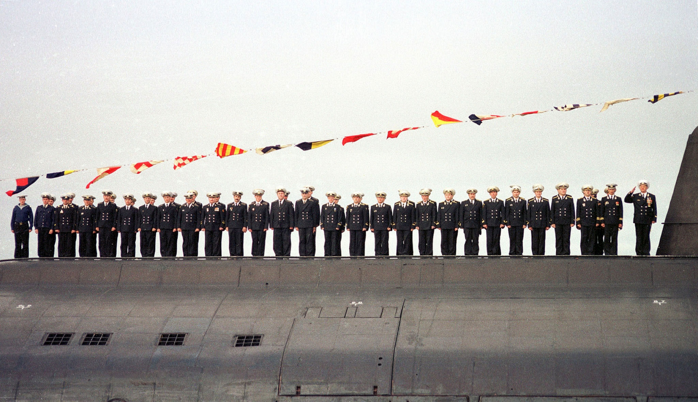 Sailors stand in a line atop their submarine in uniform