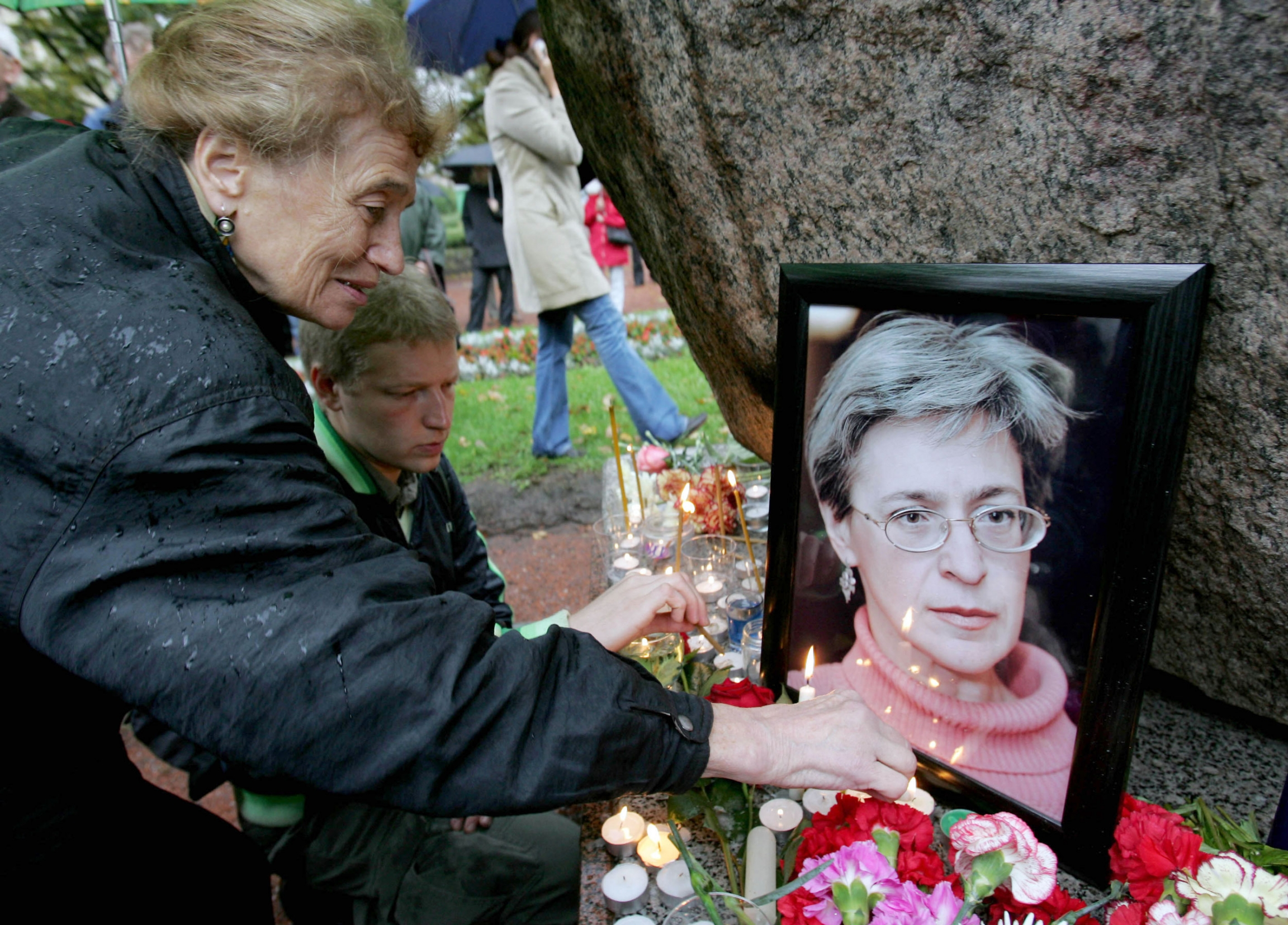 A woman lights a candle next to a framed image of Russian journalist Anna Politkovsaya