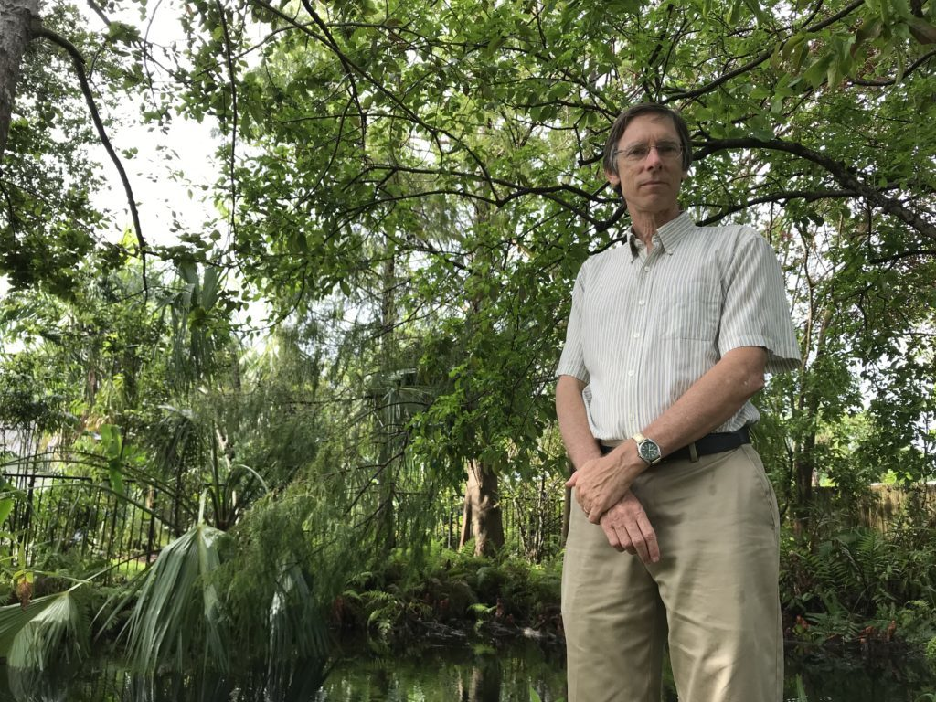 A portrait of Philip Stoddard, a biologist at Florida International University and mayor of South Miami, standing in his tree-filled backyard in 2017.