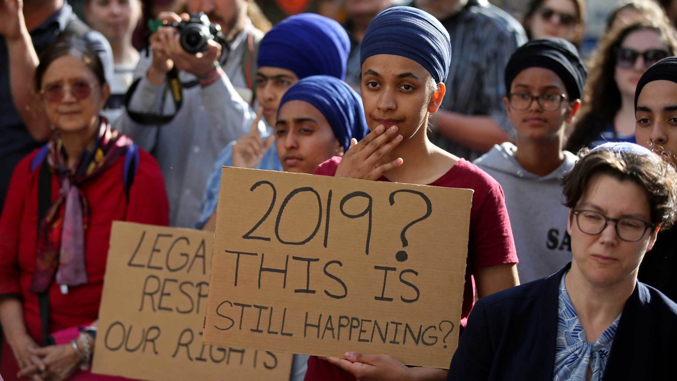 Protesters hold signs that 2019? This is still happening?