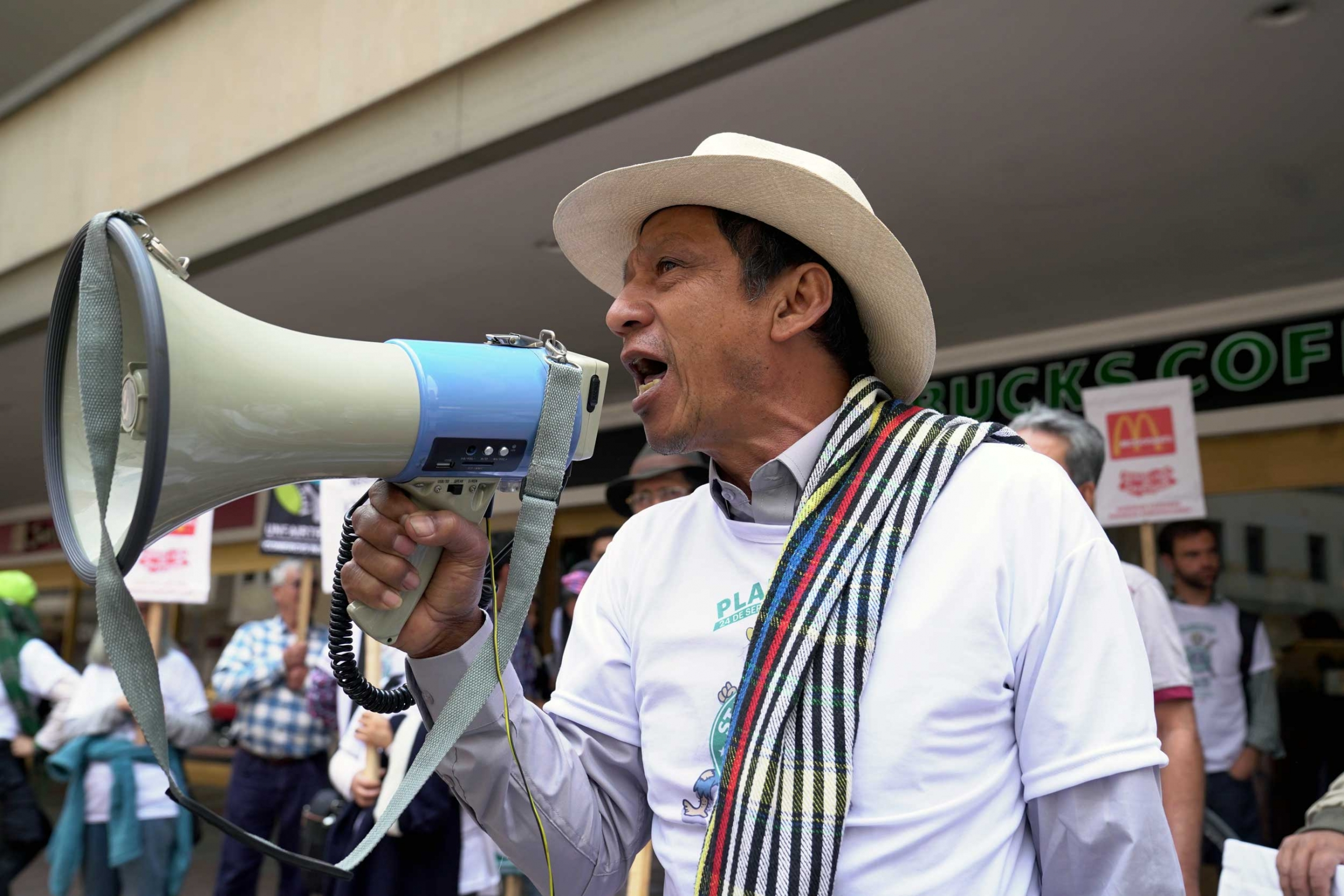 A man in a straw hat holds a megaphone outside a Starbucks coffee.