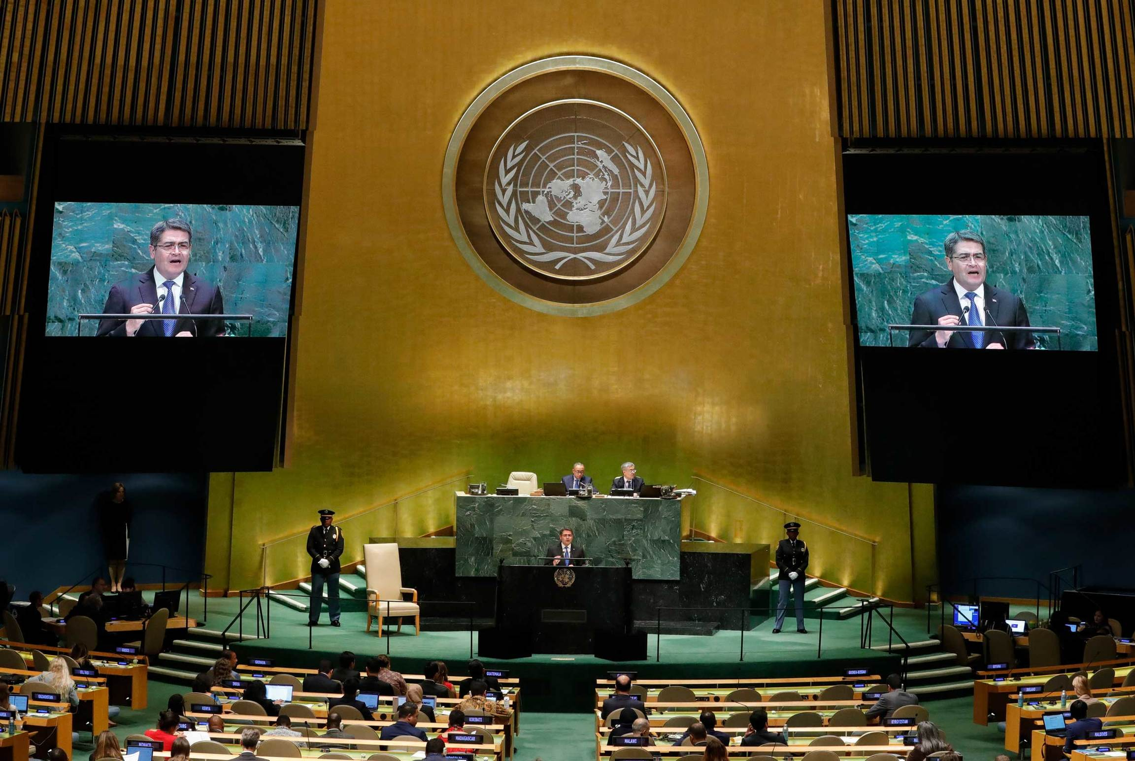 A man speaks at the UN. His image is seen in two screens at left and right of the stage.
