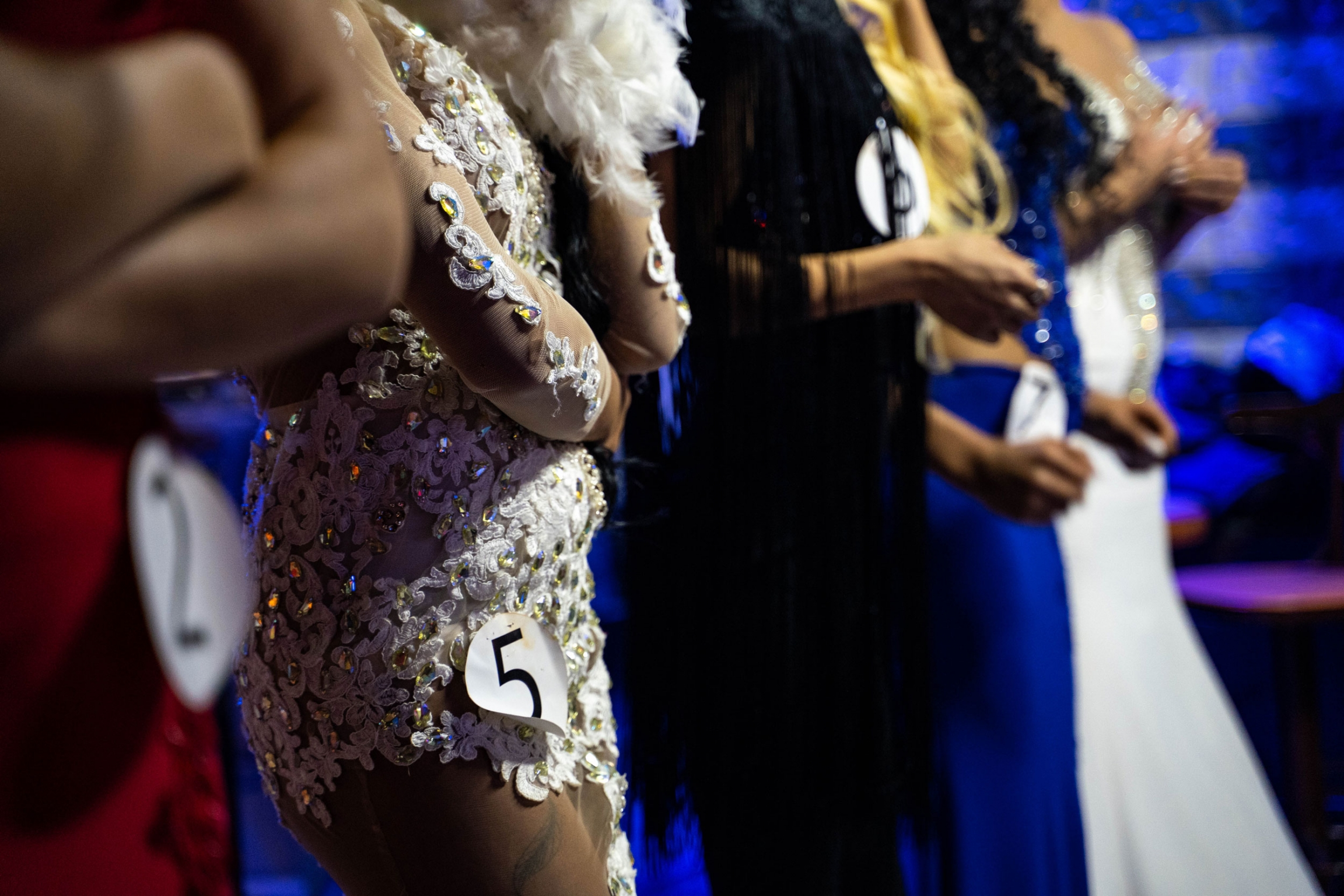 Several transgender women are shown standing side by side with numbers attached to their dresses.